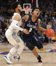 Marquette guard Markus Howard fouls Georgetown guard James Akinjo. Akinjo had 20 of his 25 points in the second half.