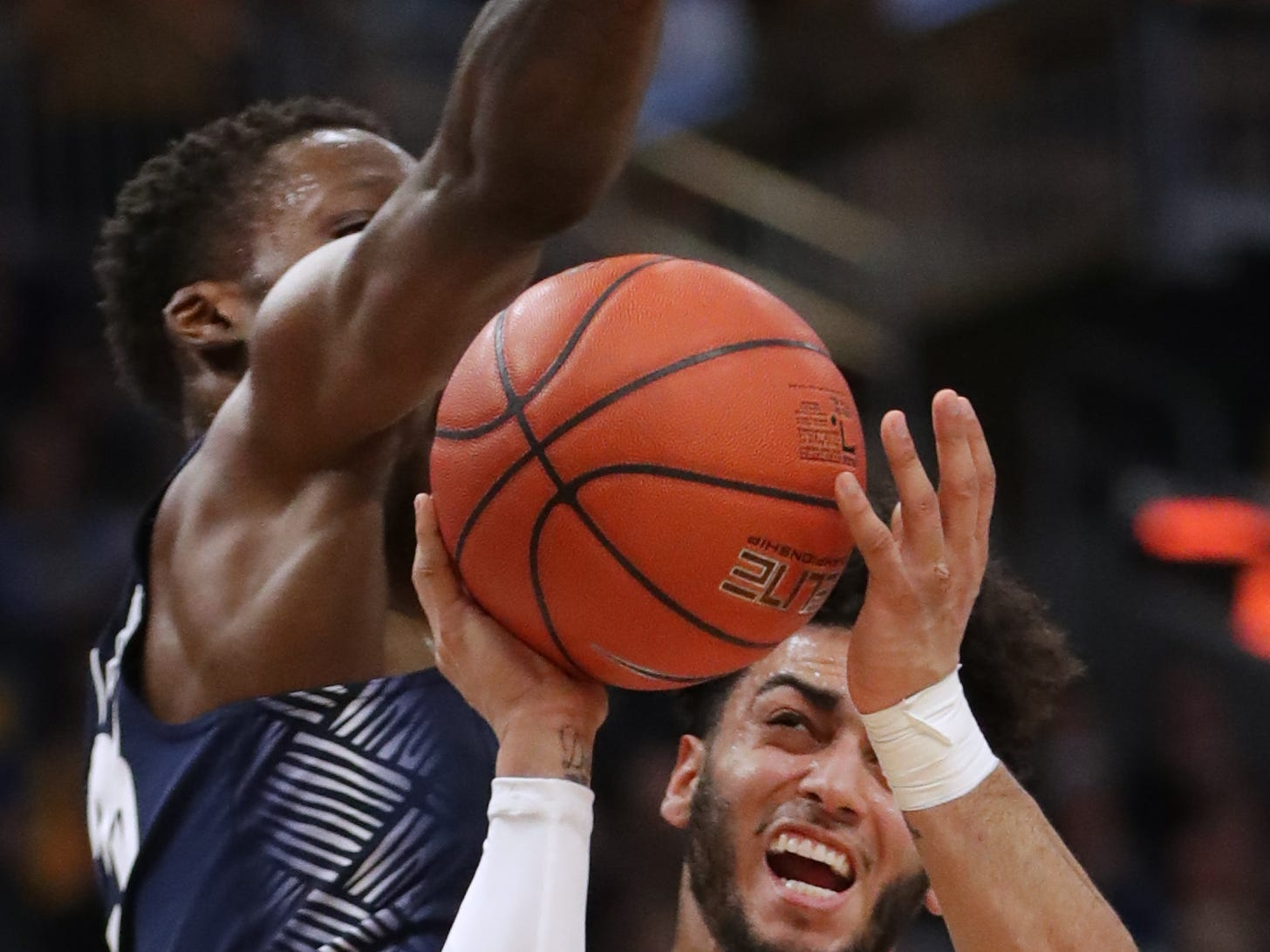Georgetown forward Josh LeBlanc tries to block a shot by Marquette guard Markus Howard.