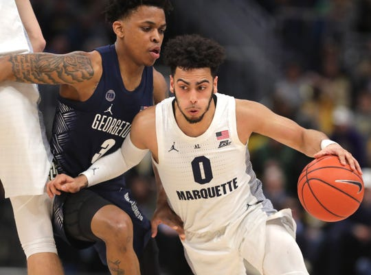 Marquette guard Markus Howard uses his arm and gets past Georgetown guard James Akinjo.