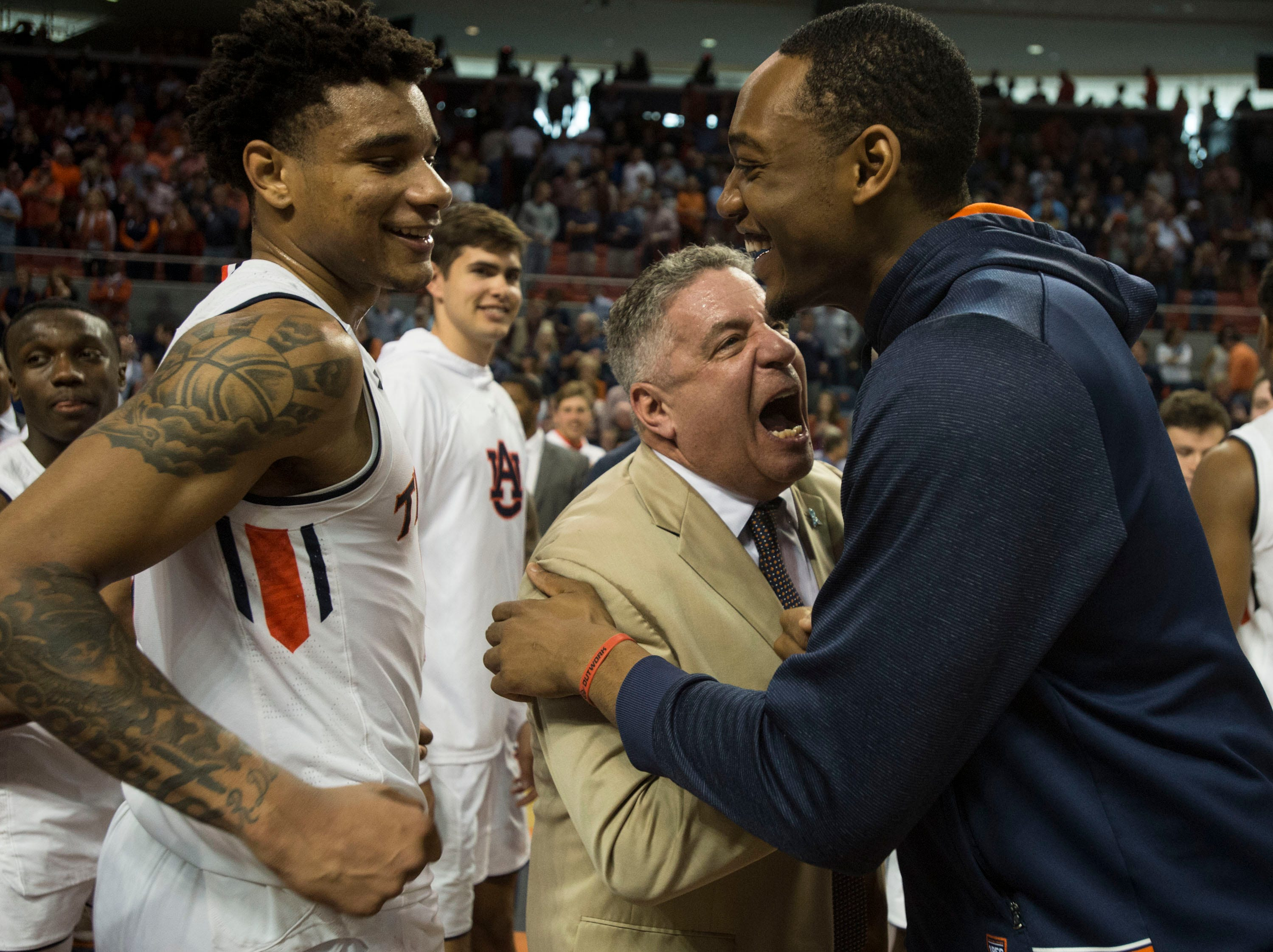 Auburn head coach Bruce Pearl, middle, and Austin Wiley, left, celebrate after the game at Auburn Arena in Auburn, Ala., on Saturday, March 9, 2019. Auburn defeated Tennessee 84-80.