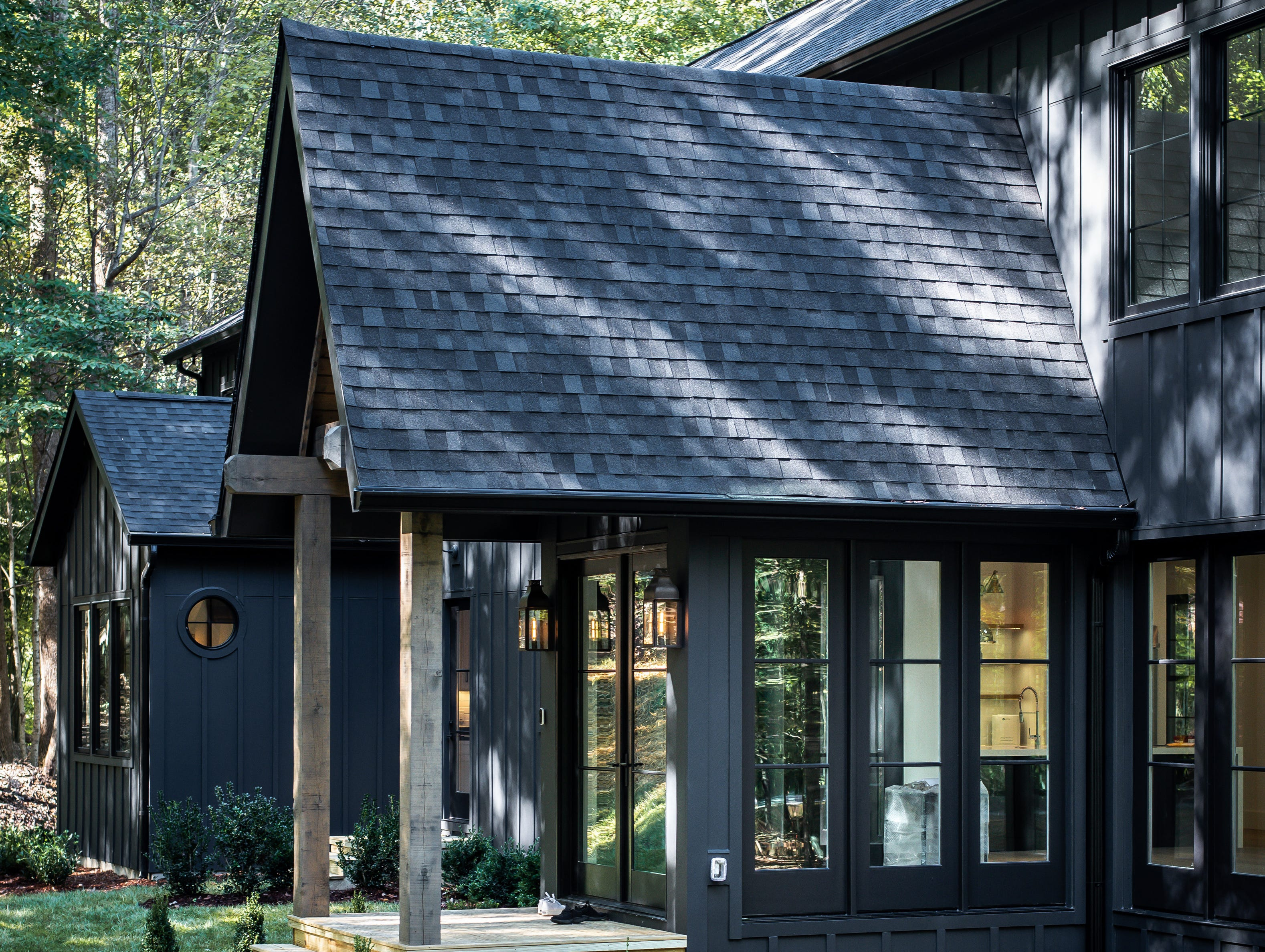 This view of the home's exterior shows how the wooded lot and shadows that are cast across the home create a very inviting and rustic setting to the home.