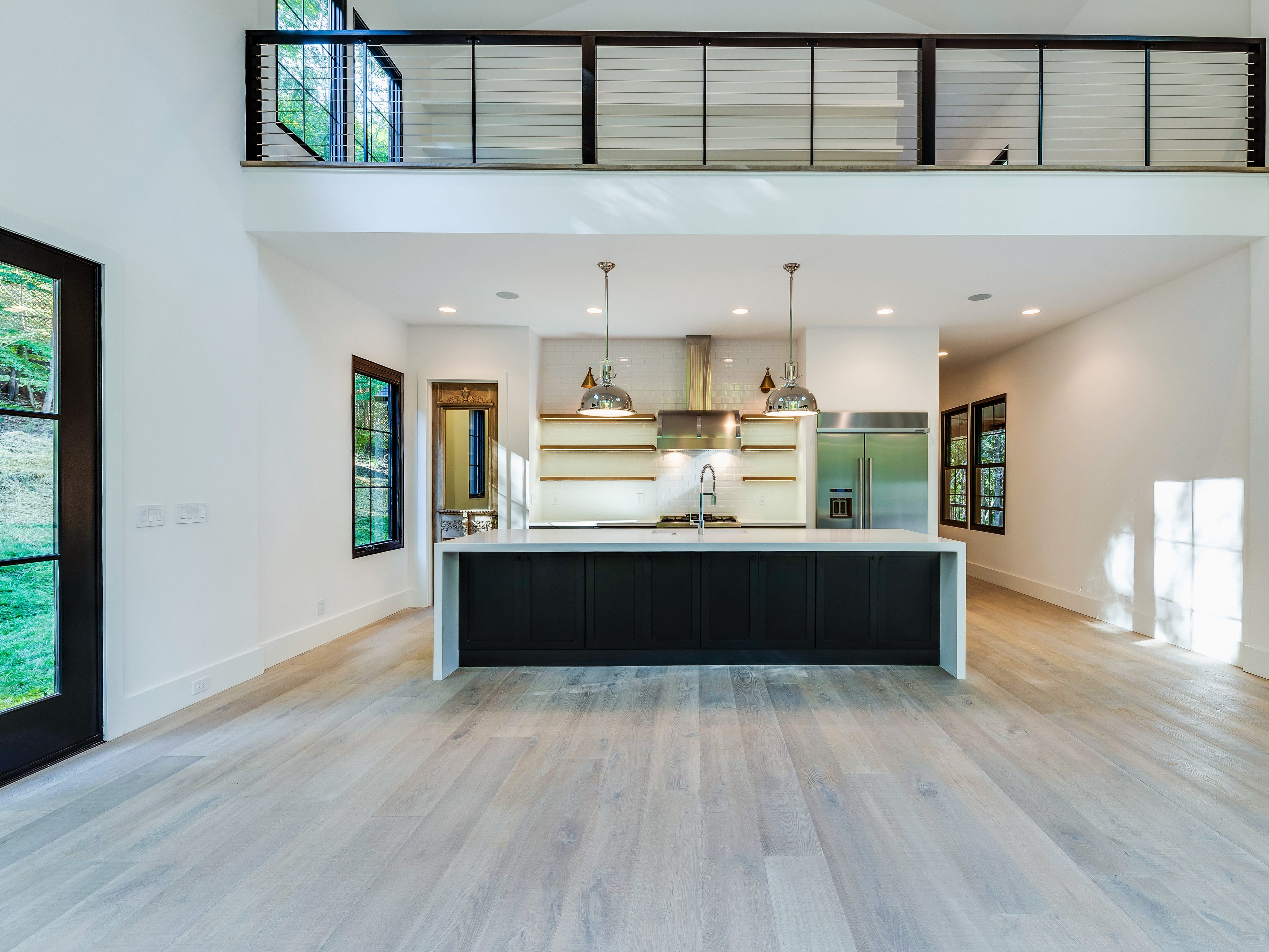 The kitchen in this farmhouse, built by Carbine and Associates, opens up to a massive living space and is topped with a loft area.