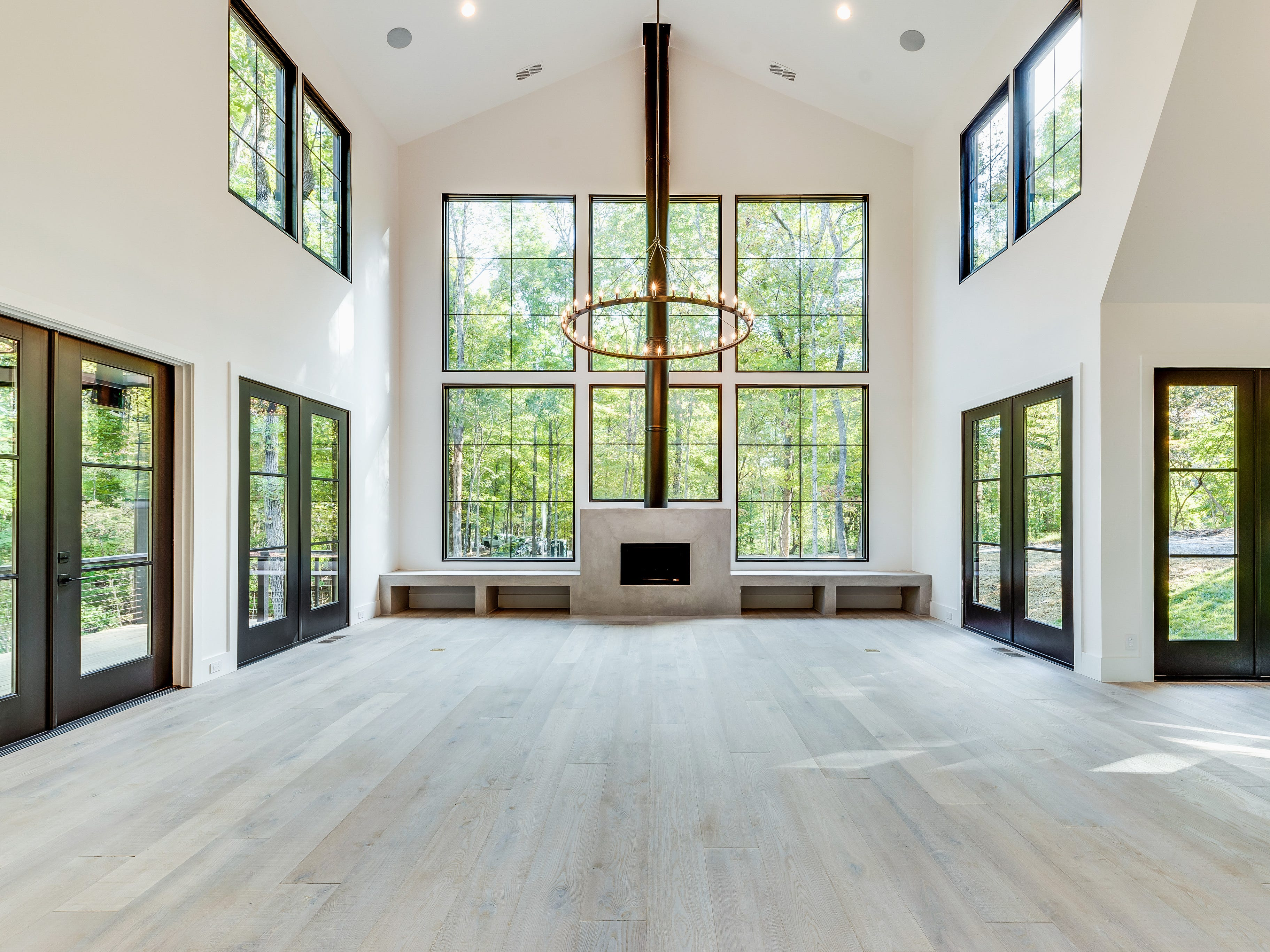 The back of this modern farmhouse features a wall of windows to let in sunlight and show off the beautiful wooded surroundings of this home.
