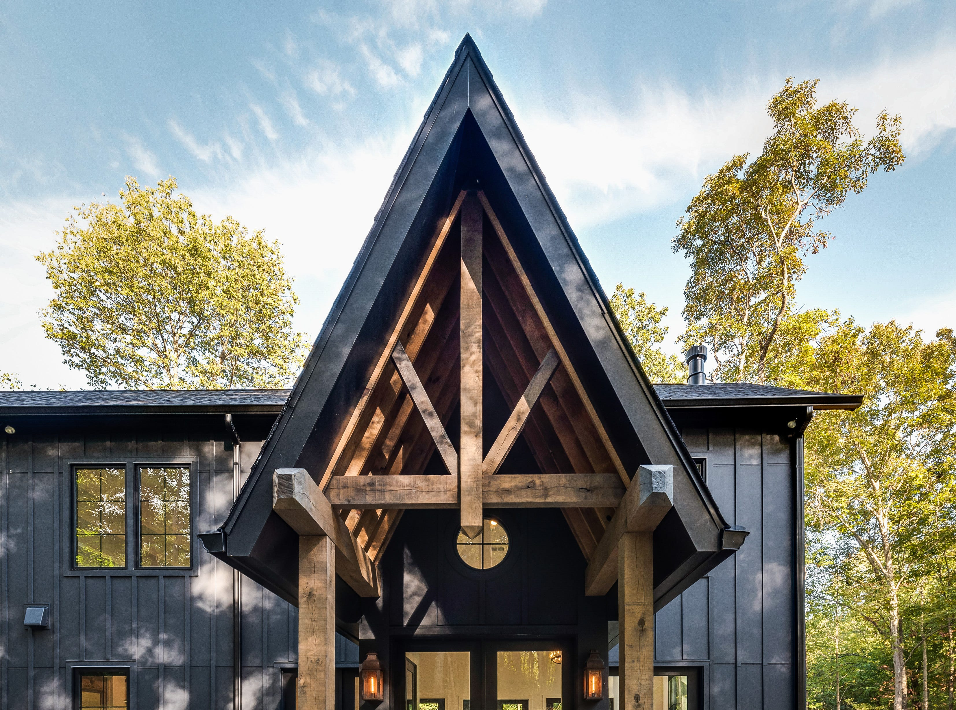 This black farmhouse also incorporates natural elements such as this wood-framed entryway.