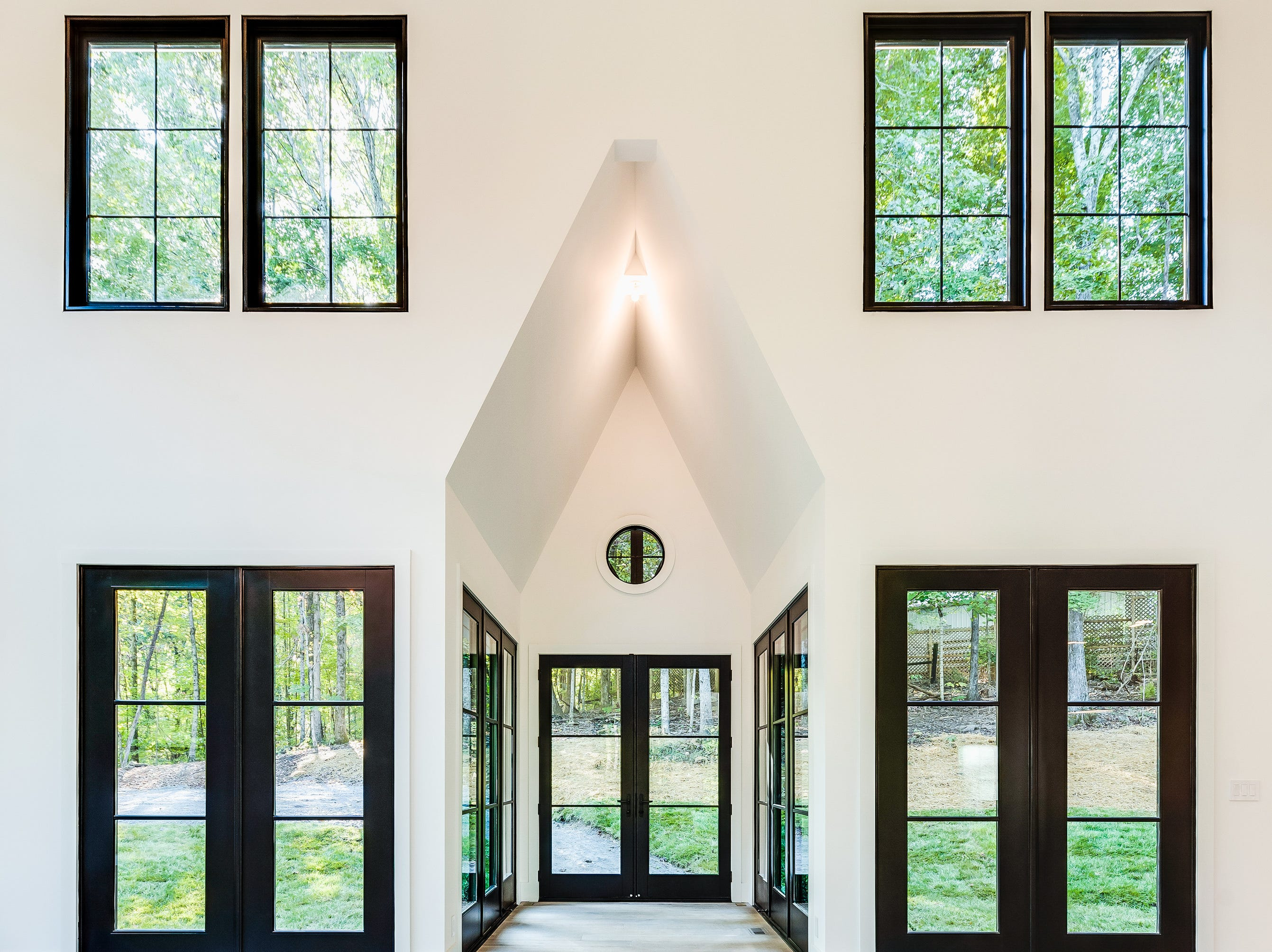 The inside of the farmhouse is drastically different from the exterior, with ample windows and stark white paint and light flooring with contrasting black window panes for a dramatic effect.