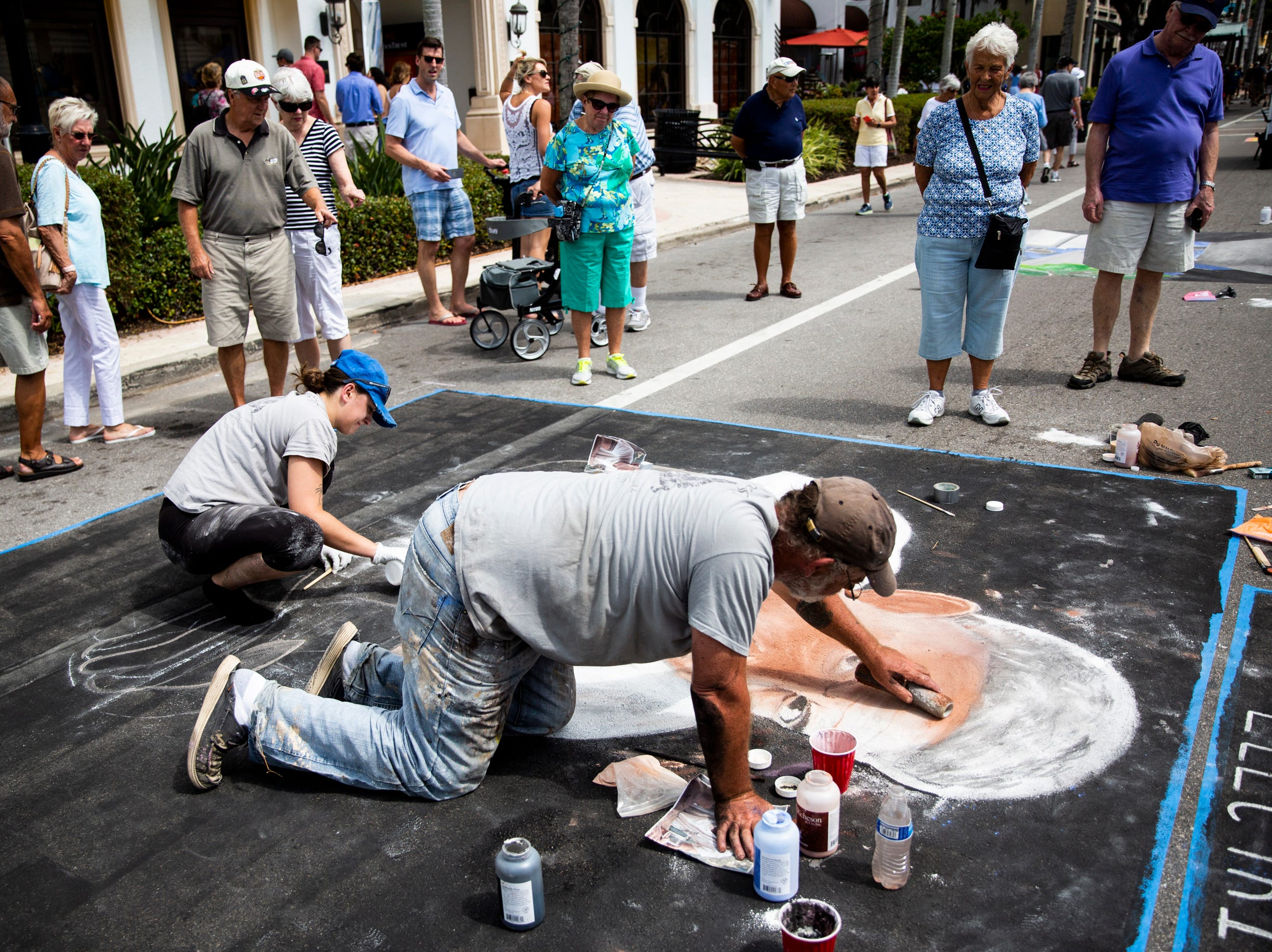 A crowd gathers to watch Erik Schlake and his daughter Allison Schlake work on a chalk portrait of Anthony Bourdain during the Naples Chalk Art festival on Fifth Avenue South on Saturday, March 9, 2019.