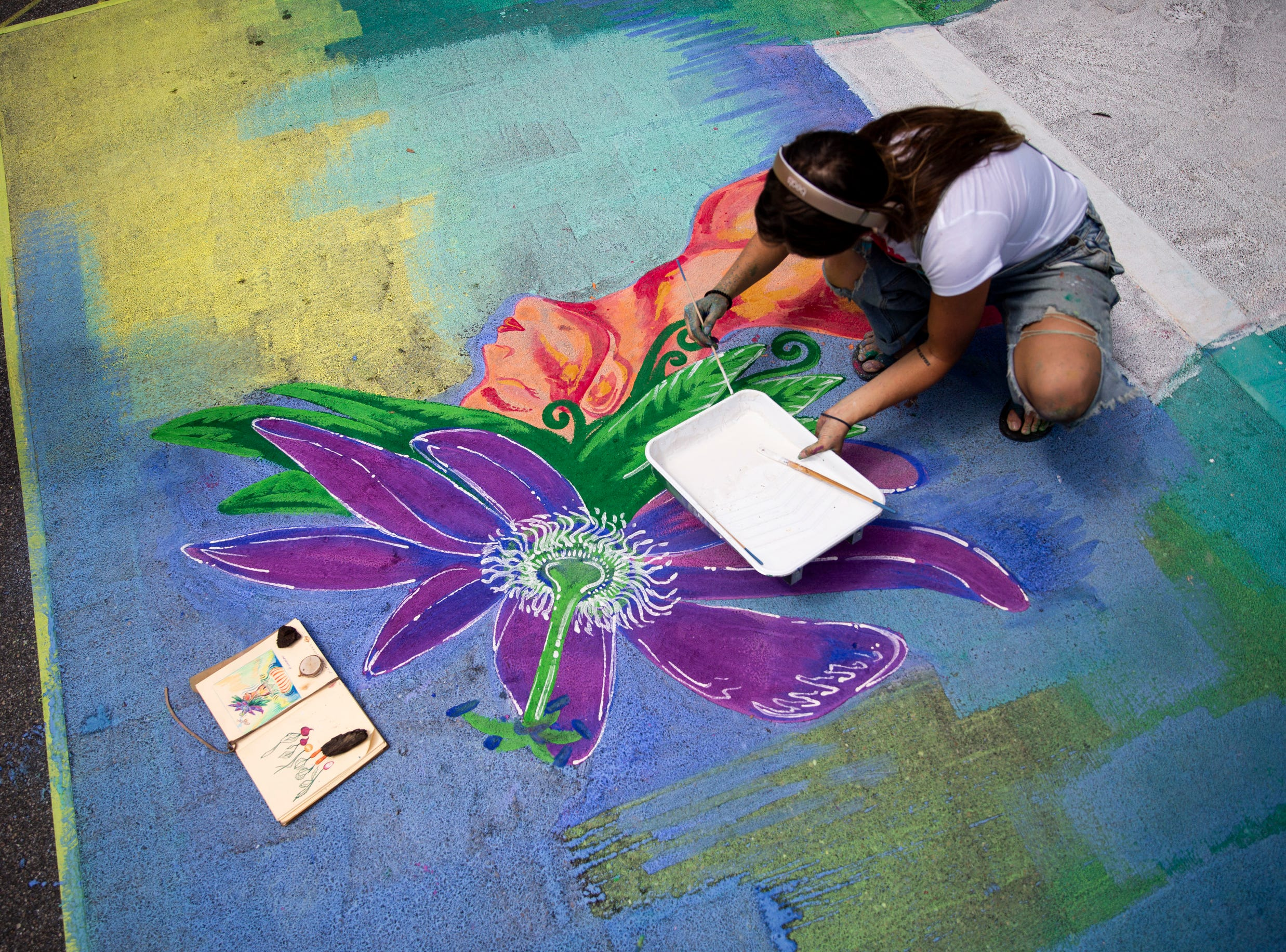 Jessica Perez works on her chalk artwork using her sketch book for reference during the Naples Chalk Art festival on Fifth Avenue South on Saturday, March 9, 2019.