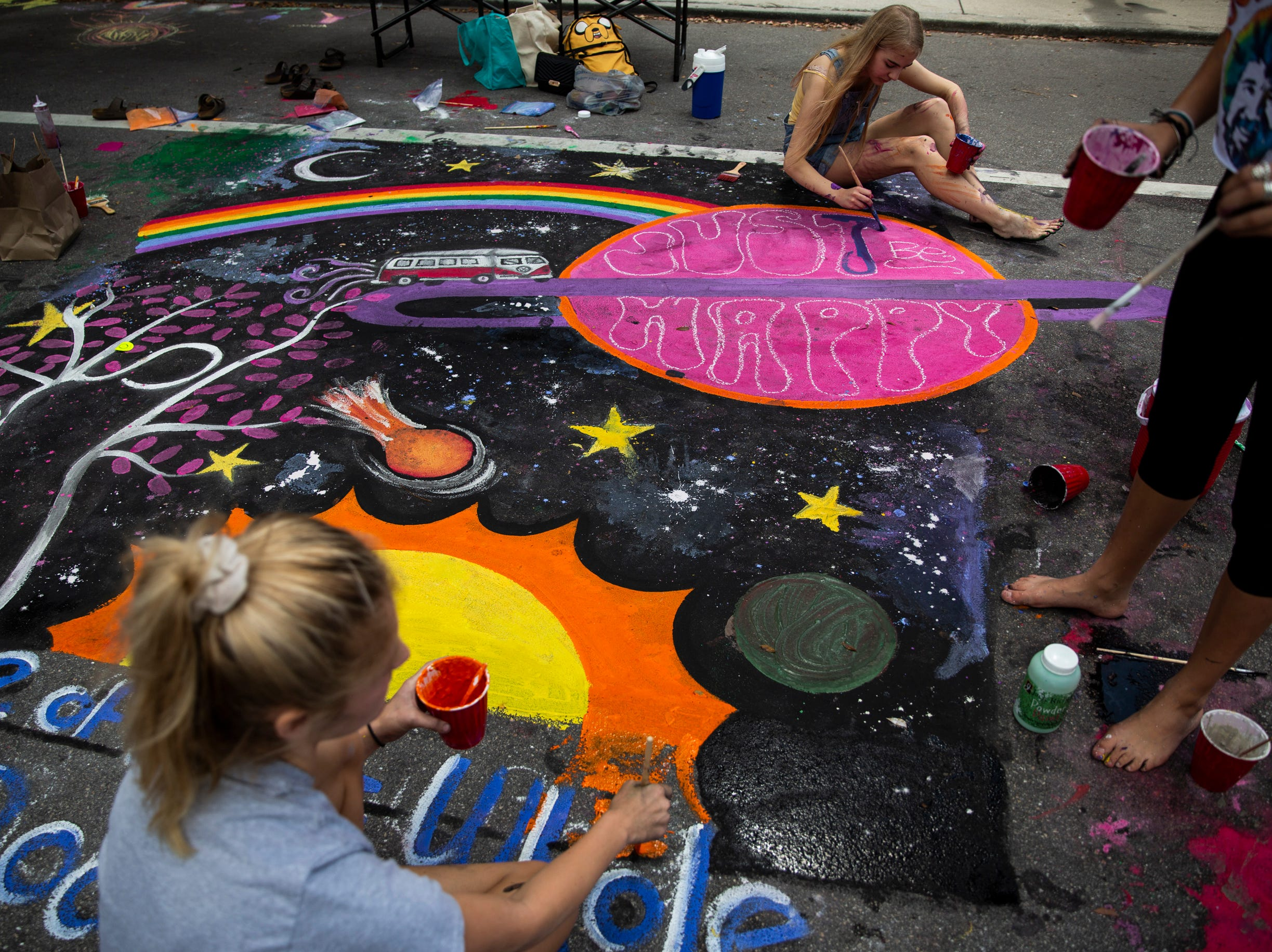 From left to right, Naples High School sophomores Gala Gibson, Norah Winogrodzki, and Grace Harris work on their chalk artwork during the Naples Chalk Art festival on Fifth Avenue South on Saturday, March 9, 2019.