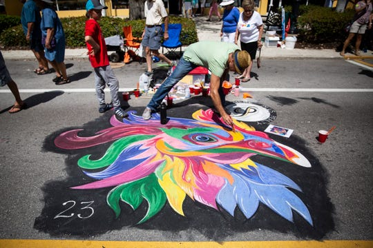 Jaden Gallus, 11, watches as his dad Eric Gallus puts the finishing touches on their chalk chicken during the Naples Chalk Art festival on Fifth Avenue South on Saturday, March 9, 2019. Jaden said he chose to do a chicken because his family has 23 chickens at home.