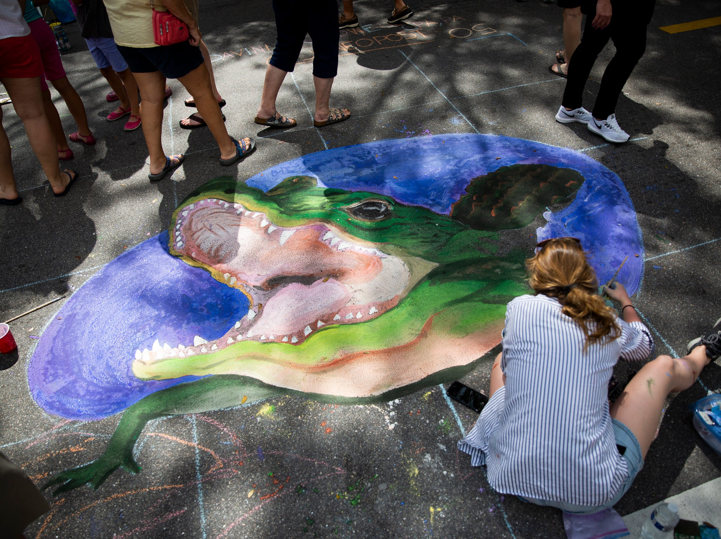Sarah Jane Post works on a chalk alligator during the Naples Chalk Art festival on Fifth Avenue South on Saturday, March 9, 2019.