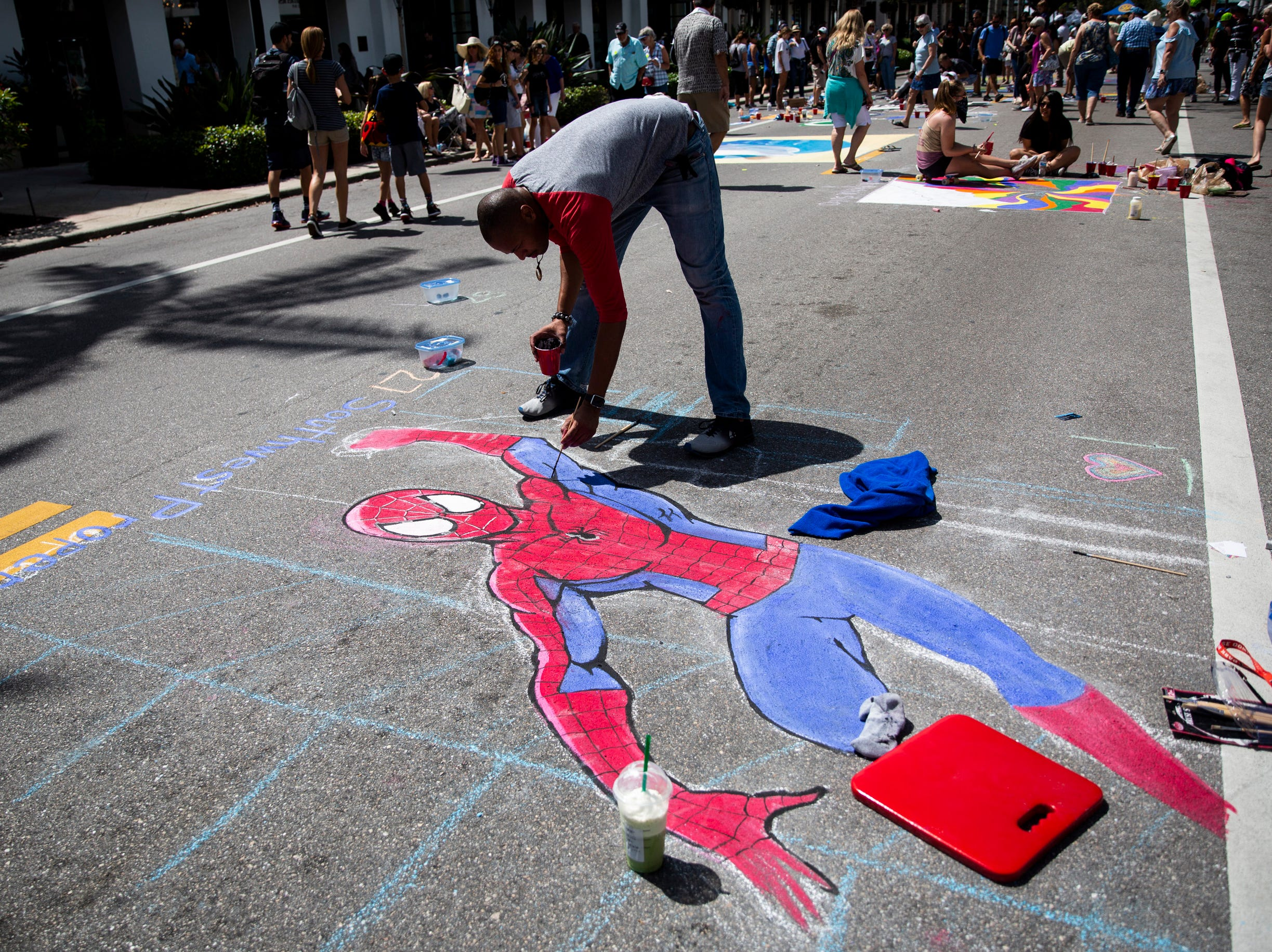Mike Sealie works on his chalk Spiderman during the Naples Chalk Art festival on Fifth Avenue South on Saturday, March 9, 2019.