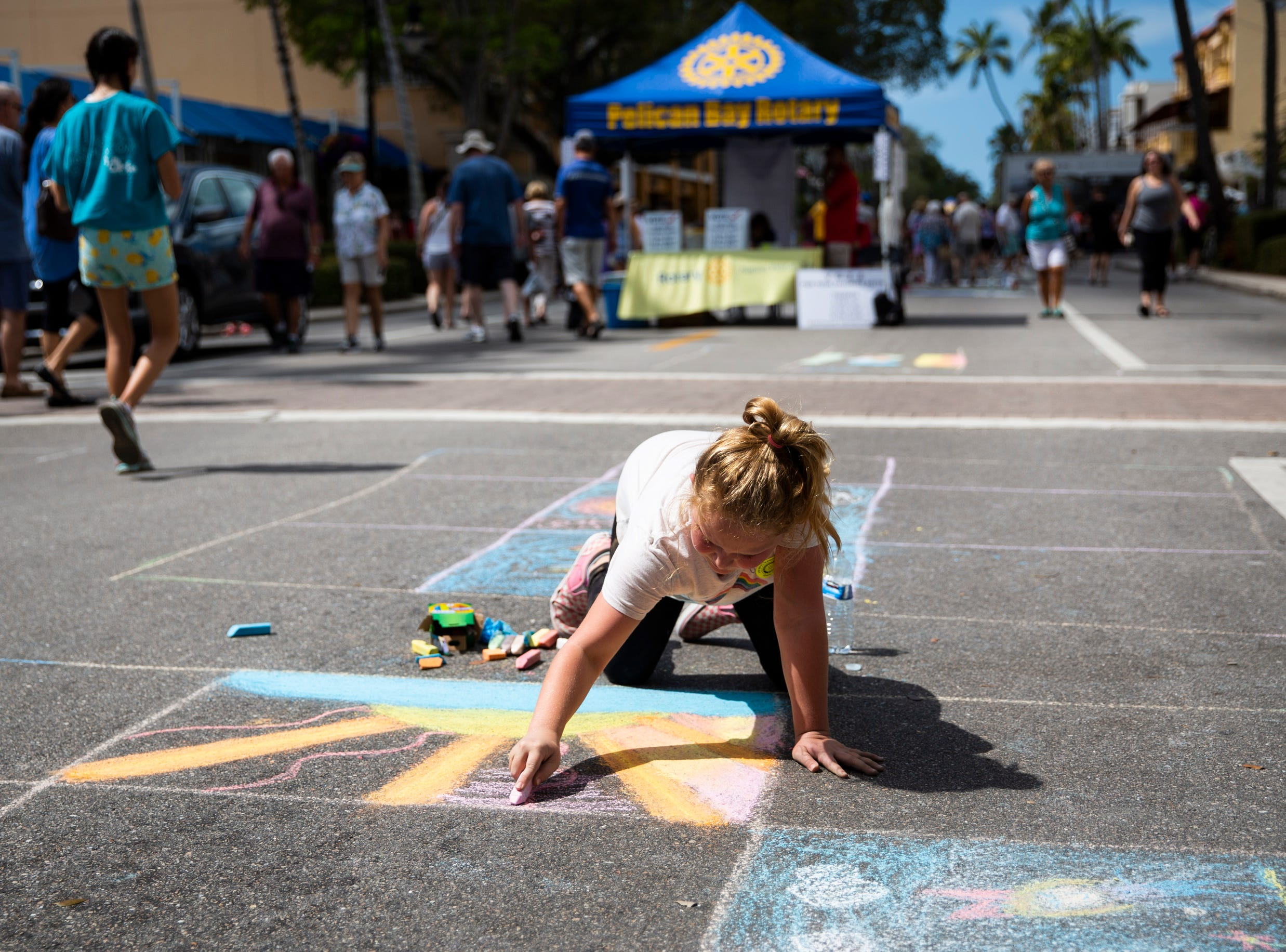 Emily Grace Brown, 9, fills in a square with a chalk sunset during the Naples Chalk Art festival on Fifth Avenue South on Saturday, March 9, 2019.