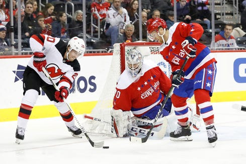 New Jersey Devils center Blake Coleman (20) shoots the puck on Washington Capitals goaltender Braden Holtby (70) as Capitals defenseman Nick Jensen (3) defends in the second period at Capital One Arena.