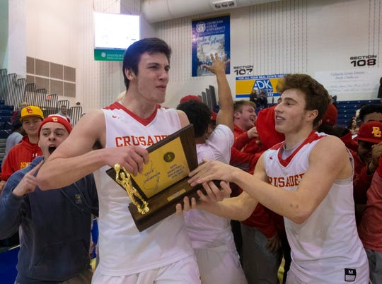Zachary Freemantle and team mates pass the trophy around as they celebrate.  Bergen Catholic Boys Basketball defeats Camden Catholic in Non-Public A Final in Toms River, NJ on March 9, 2019.