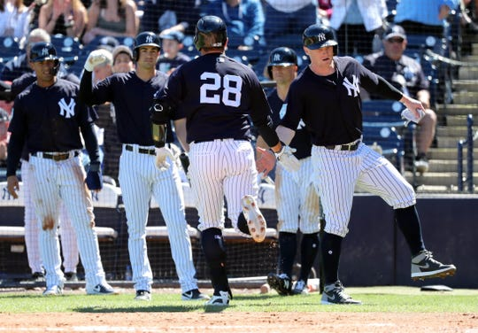 New York Yankees catcher Austin Romine (28) is congratulated by left fielder Clint Frazier (77),  second baseman Tyler Wade (14) and teammates  as he hits a 3-run home run during the second inning against the St. Louis Cardinals at George M. Steinbrenner Field on Mar 6, 2019 in Tampa, Florida.