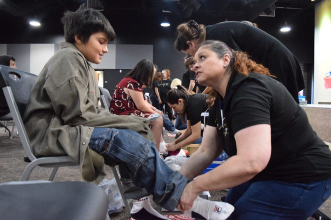 Landmark Church member Barbara Hernandez, right, outfits Tristan Bryant, 8, with new shoes at the Soles4Souls event on Saturday, March 9, 2019 at Las Cruces First Assembly of God.