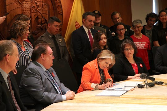 New Mexico Gov. Michelle Lujan Grisham on Friday, March 8, 2019, signs into law a bill that expands mandatory background checks for people purchasing guns in New Mexico.