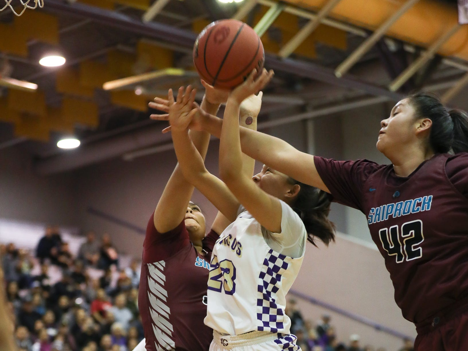 Kirtland Central's Avery Begay is fouled by Shiprock's Doniah Gruber (33) and Evette Lansing (42) during Friday's 4A playoff opener at Bronco Arena in Kirtland.