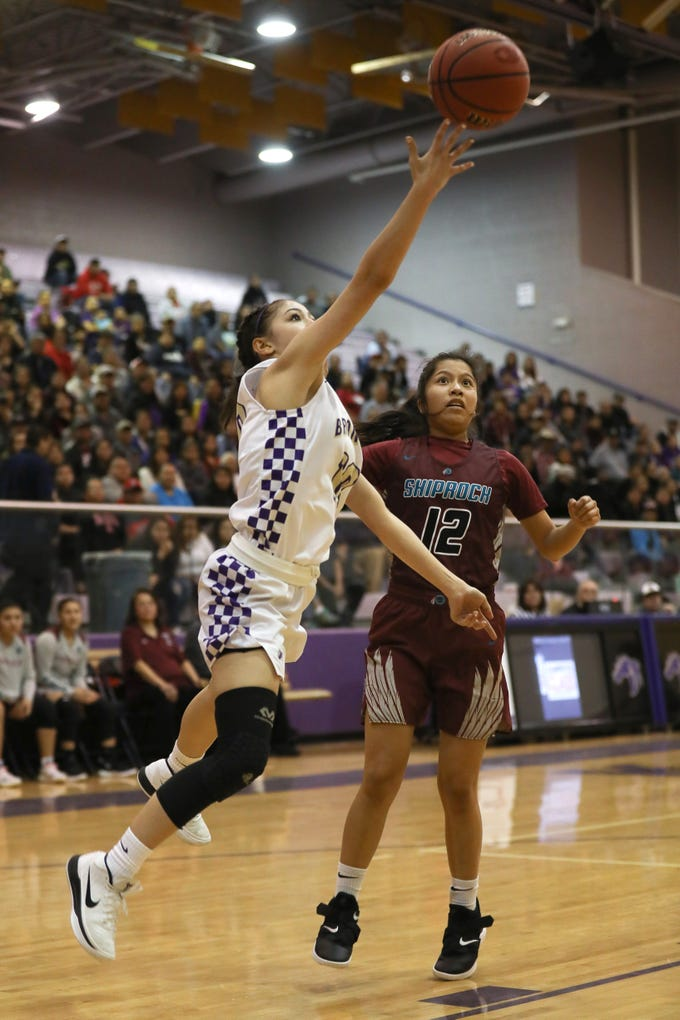 Kirtland Central's Monique Shim drives by Shiprock's Kimora Tso for a layup during Friday's 4A playoff opener at Bronco Arena in Kirtland.