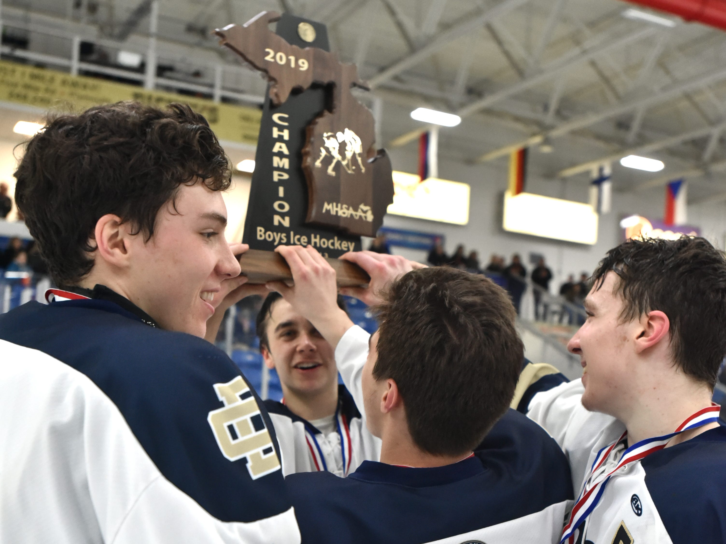 Country Day captains raise their Division 3 MHSAA state championship trophy on March 9 at USA Hockey Arena in Plymouth, MI.