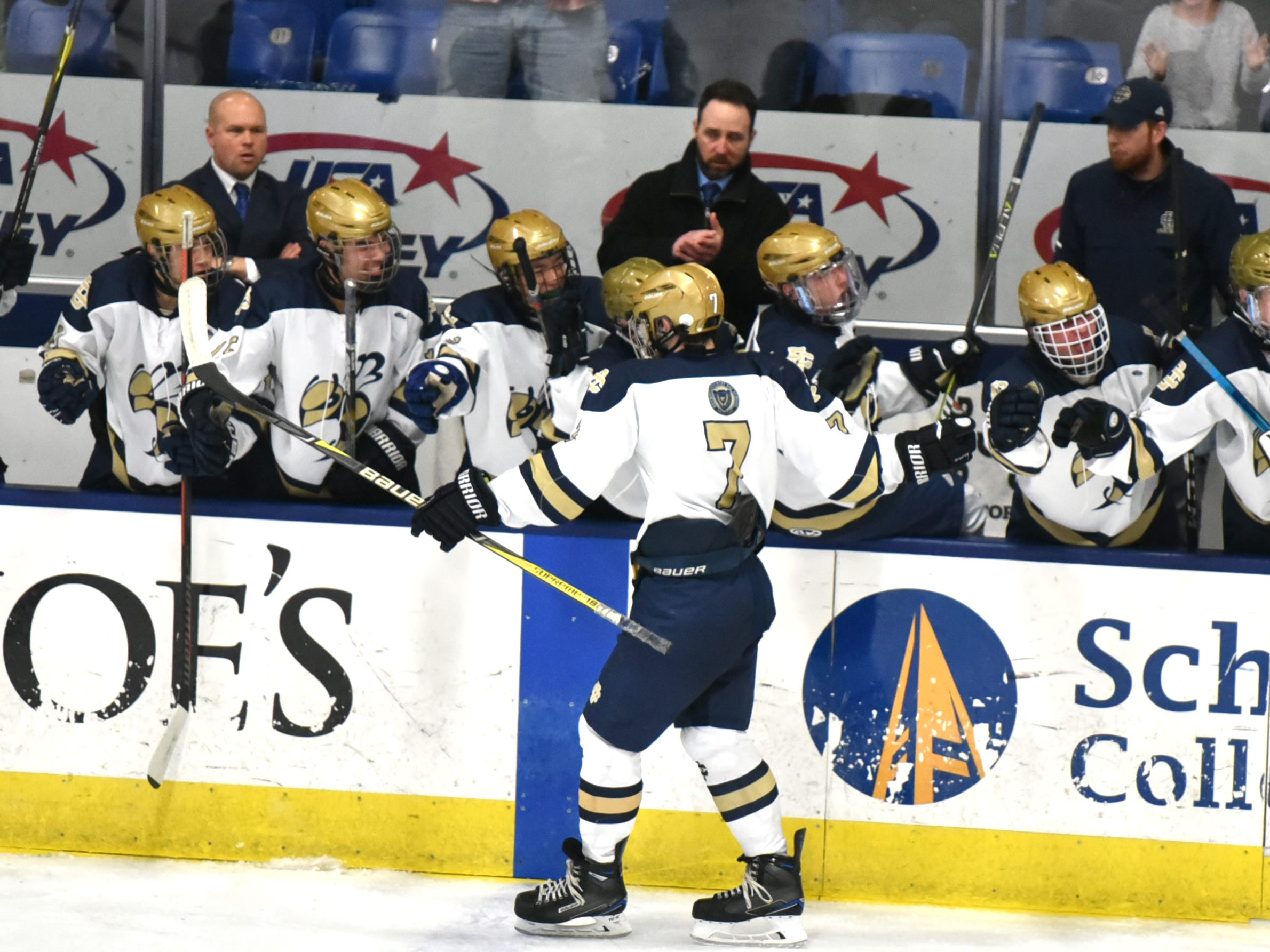 Country Day hockey player Dalas Hood celebrates his - and DCD's second goal with his teammates on the bench.