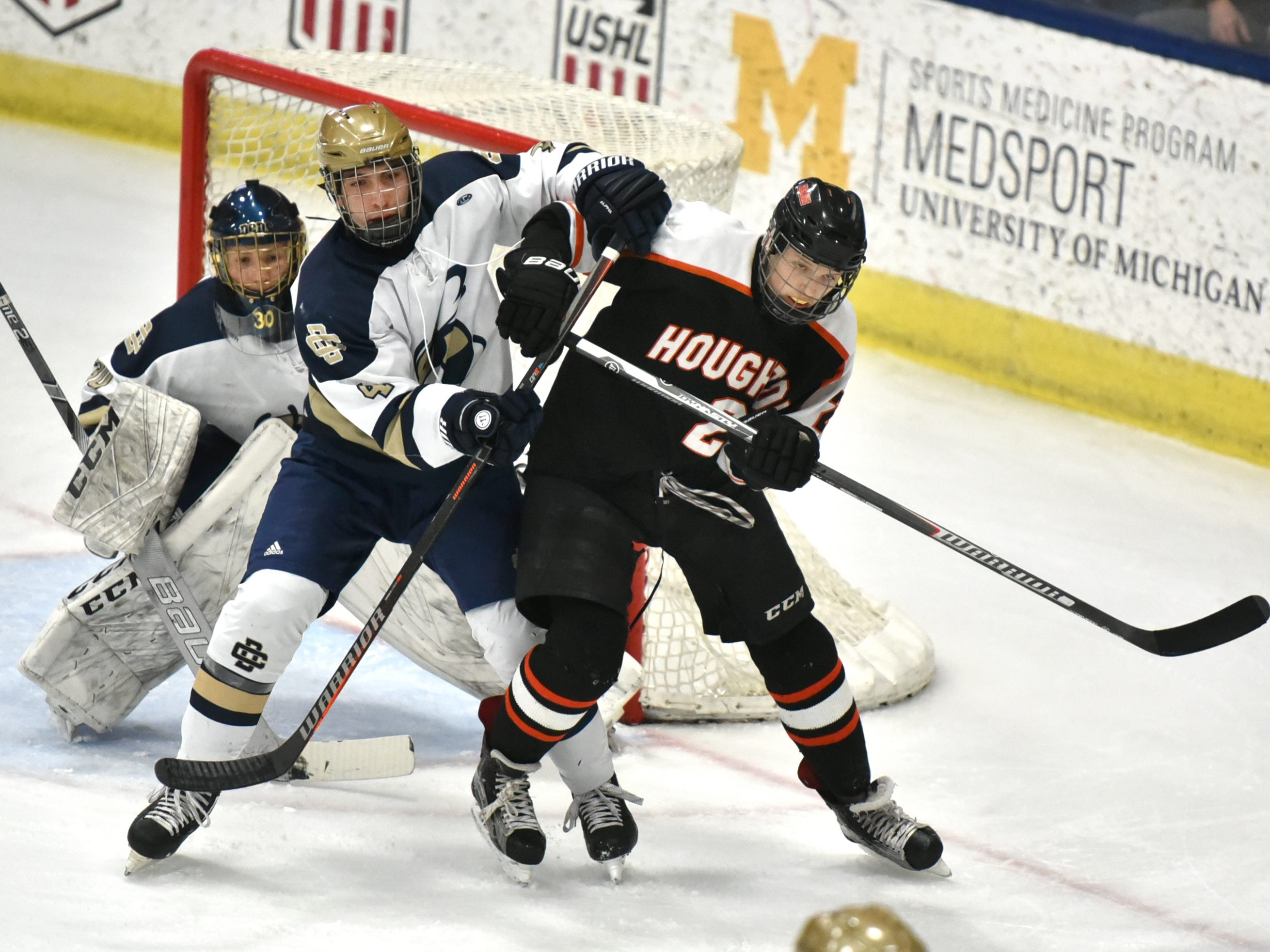Detroit Country Day School defenseman Gino Sessa, center, tries to boot Houghton's Seth Francois out of the way of his goalie - Sam Evola during DCD's March state final MHSAA game at USA Hockey Arena in Plymouth, MI. Country Day won its second straight championship 4-1.