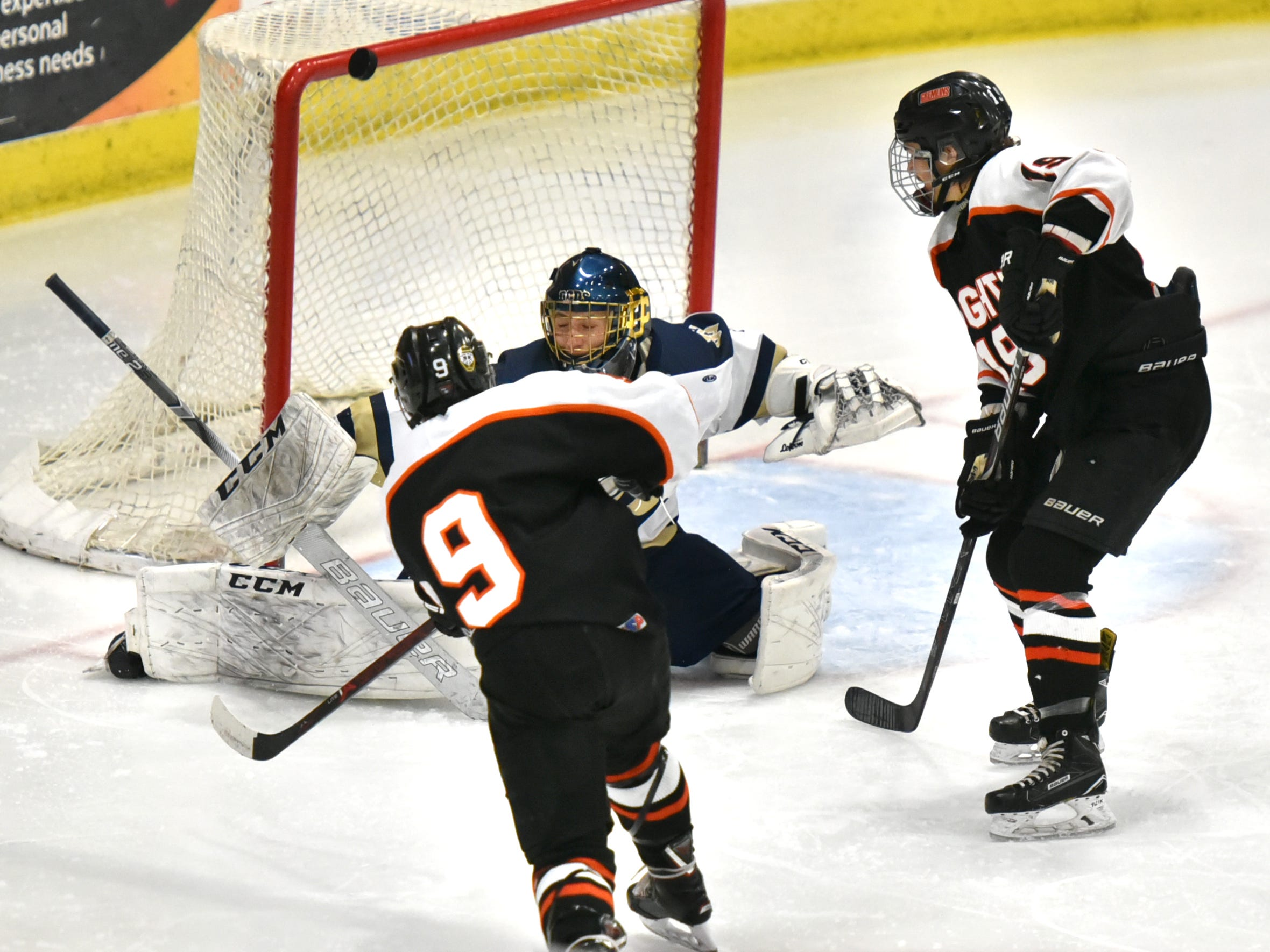 With two Houghton players bearing down on him including Justin Norkol, right, DCD goalie Sam Evola makes a pad save - and the puck heads up over the cross bar.