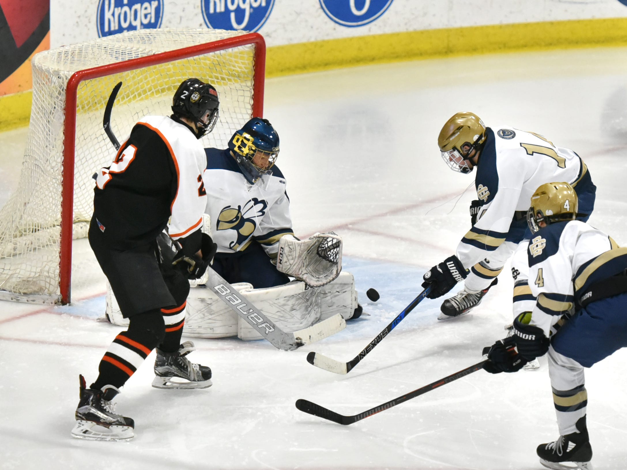With Houghton's Seth Francois to his right and a lot of action and the puck to his left - Detroit Country Day's goalie Sam Evola tries to keep an eye on everything on March 9 at USA Hockey Arena.