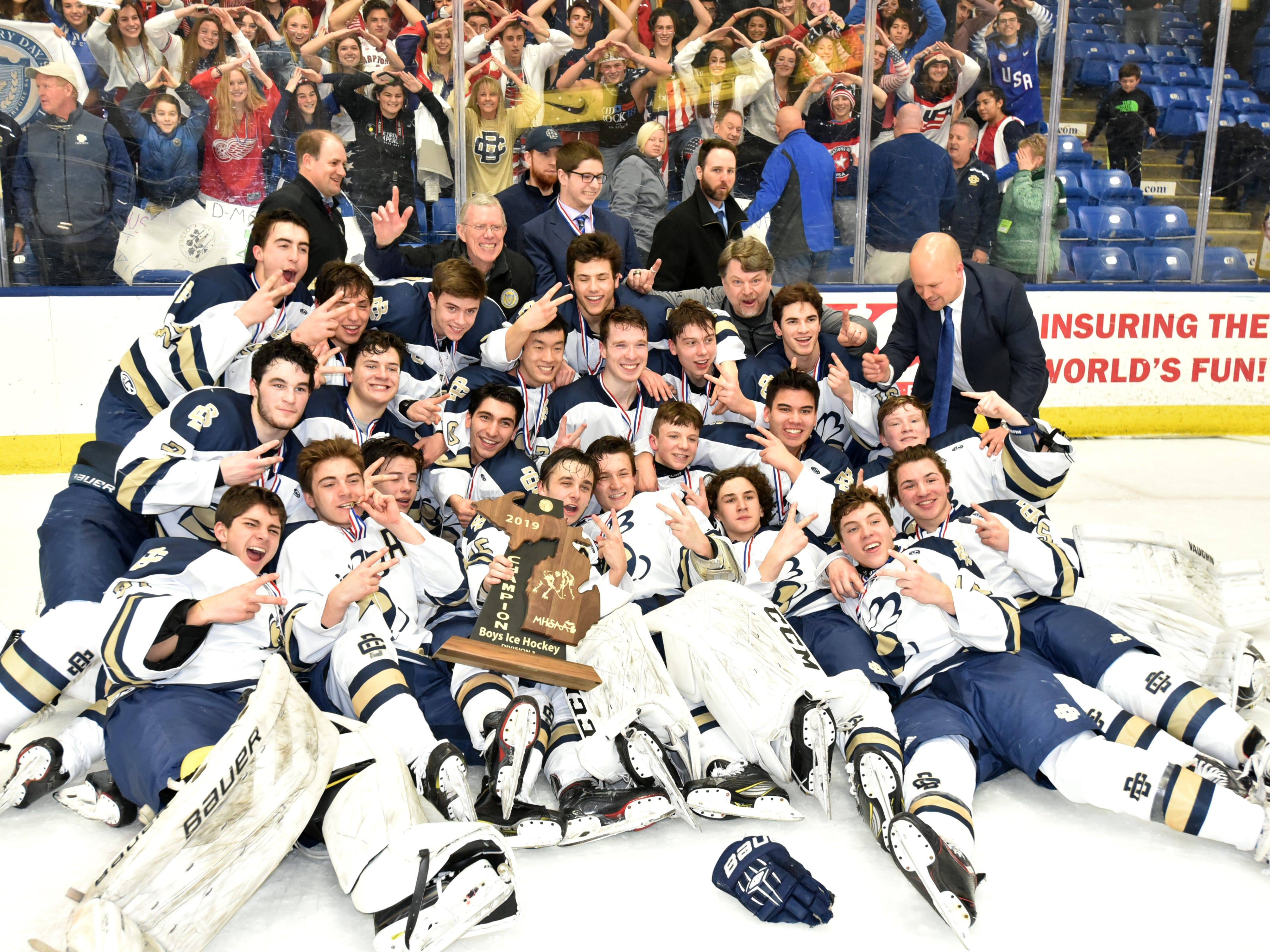 The Detroit Country Day School hockey team, with two fingers raised, celebrates its second consecutive championship on March 9, 2019.