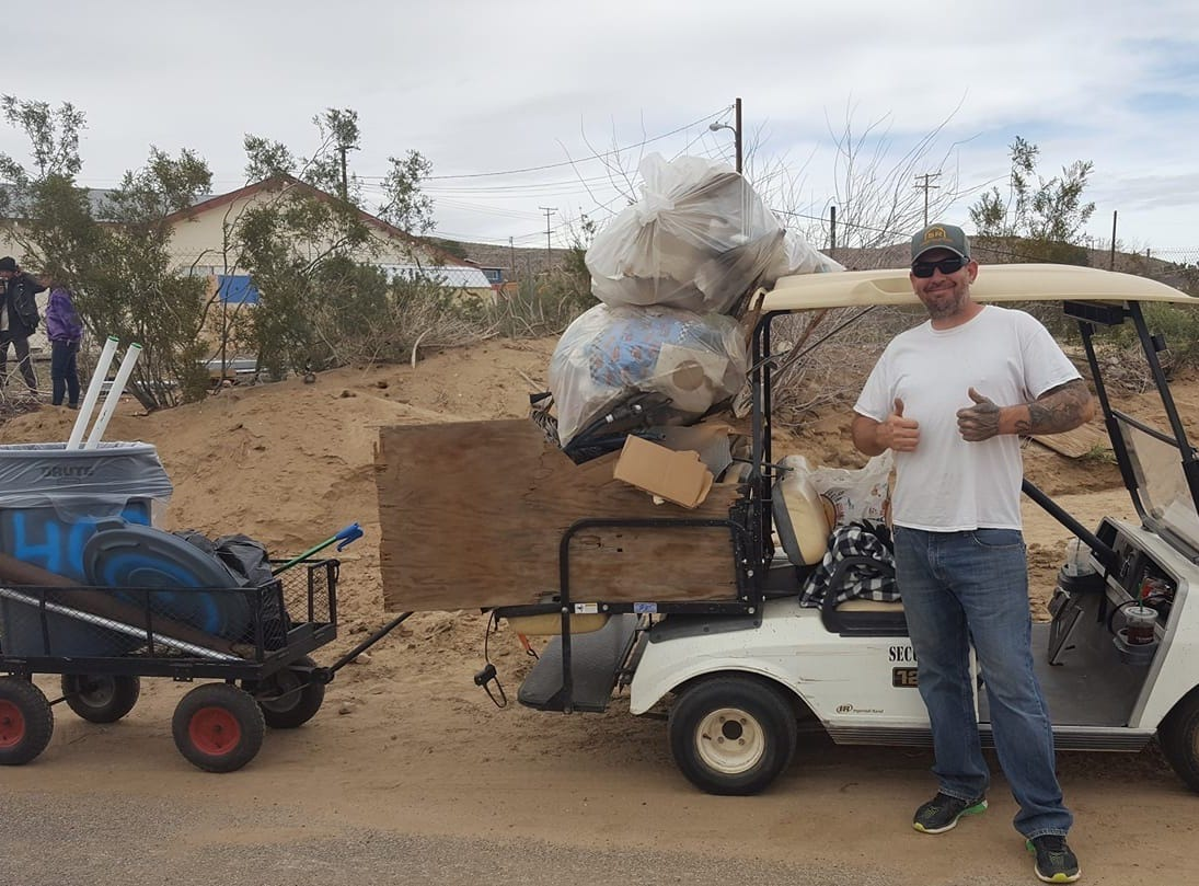Colin Sauter poses with trash collected in the high desert.