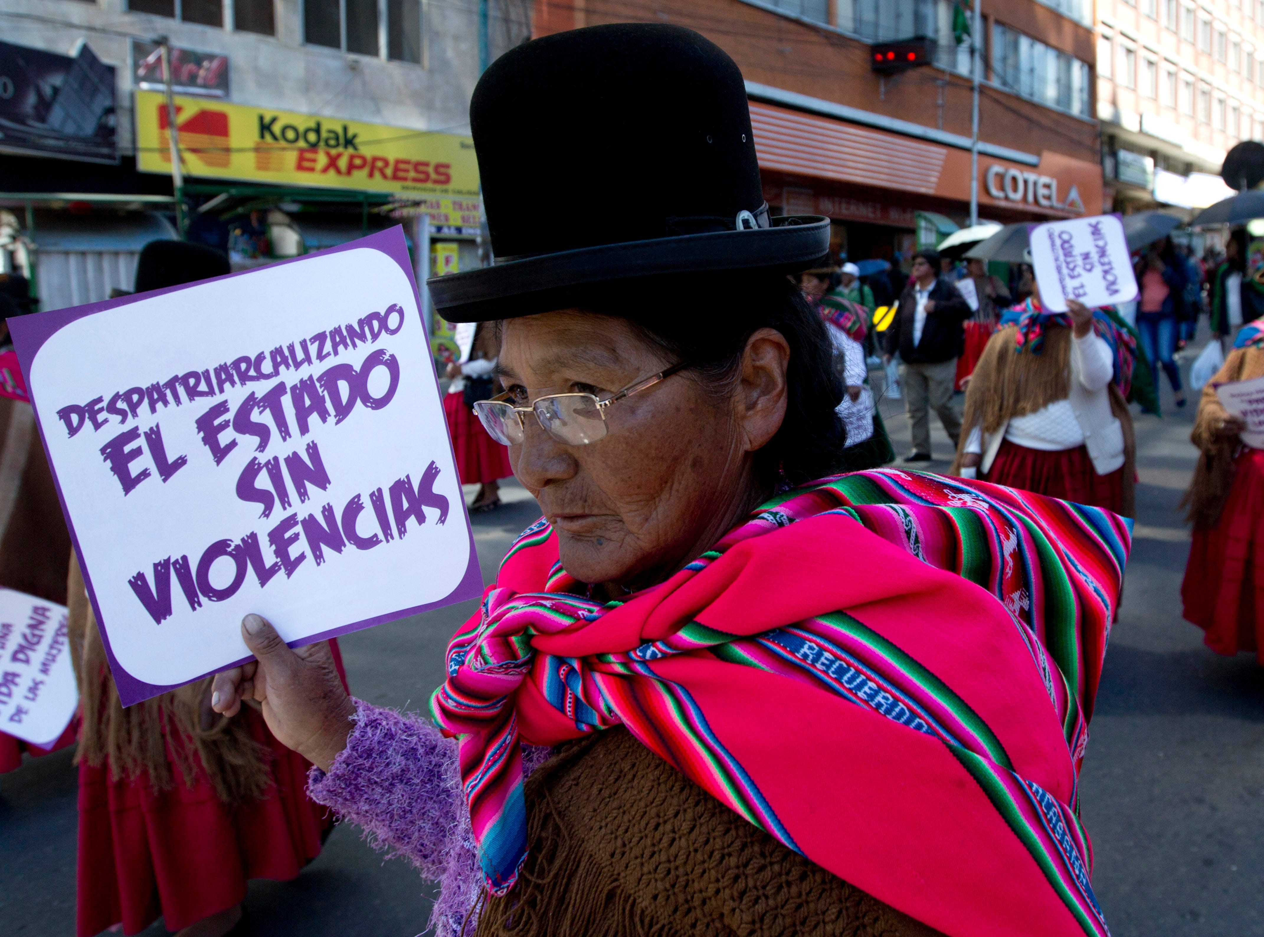 """An Aymara woman holds a sign with a message that reads in Spanish: """"Dismantle the patriarchy. A state without violence,"""" during a march marking International Women's Day, in La Paz, Bolivia, Friday, March 8, 2019. The day has been sponsored by the United Nations since 1975 as millions around the world are demanding equality amid a persistent salary gap, violence and widespread inequality. (AP Photo/Juan Karita)"""