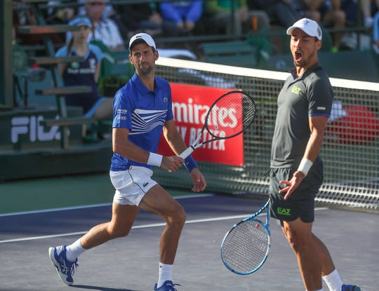 Doubles partners Novak Djokovic and Fabio Fognini react to a missed shot at the BNP Paribas Open, March 8, 2019.