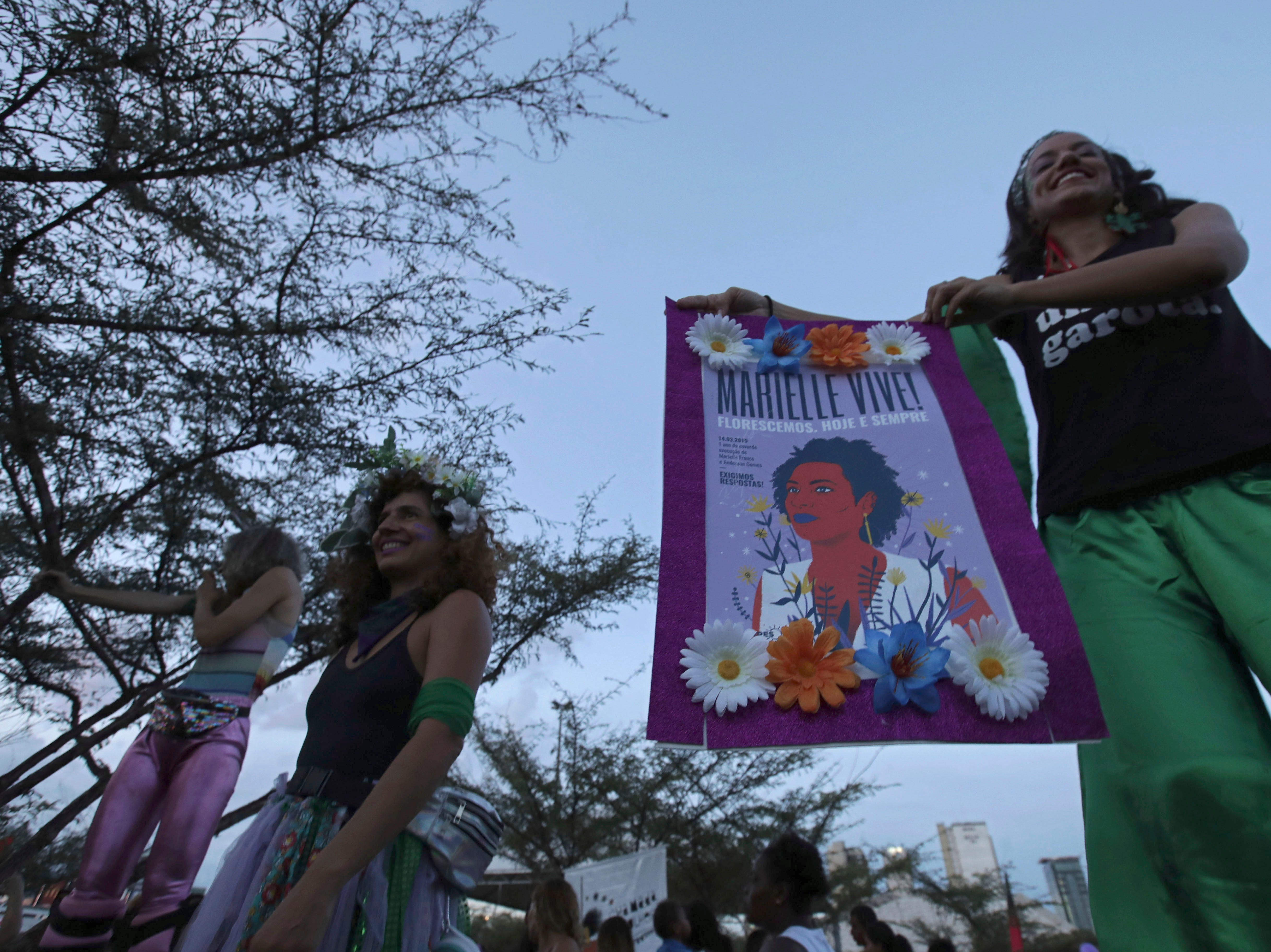 A woman carries a poster with an image of slain councilwoman Marielle Franco, during the March in Defense of Women's Rights, in celebration of International Women's Day, in Brasilia, Brazil, Friday, March 8, 2019. (AP Photo/Eraldo Peres)