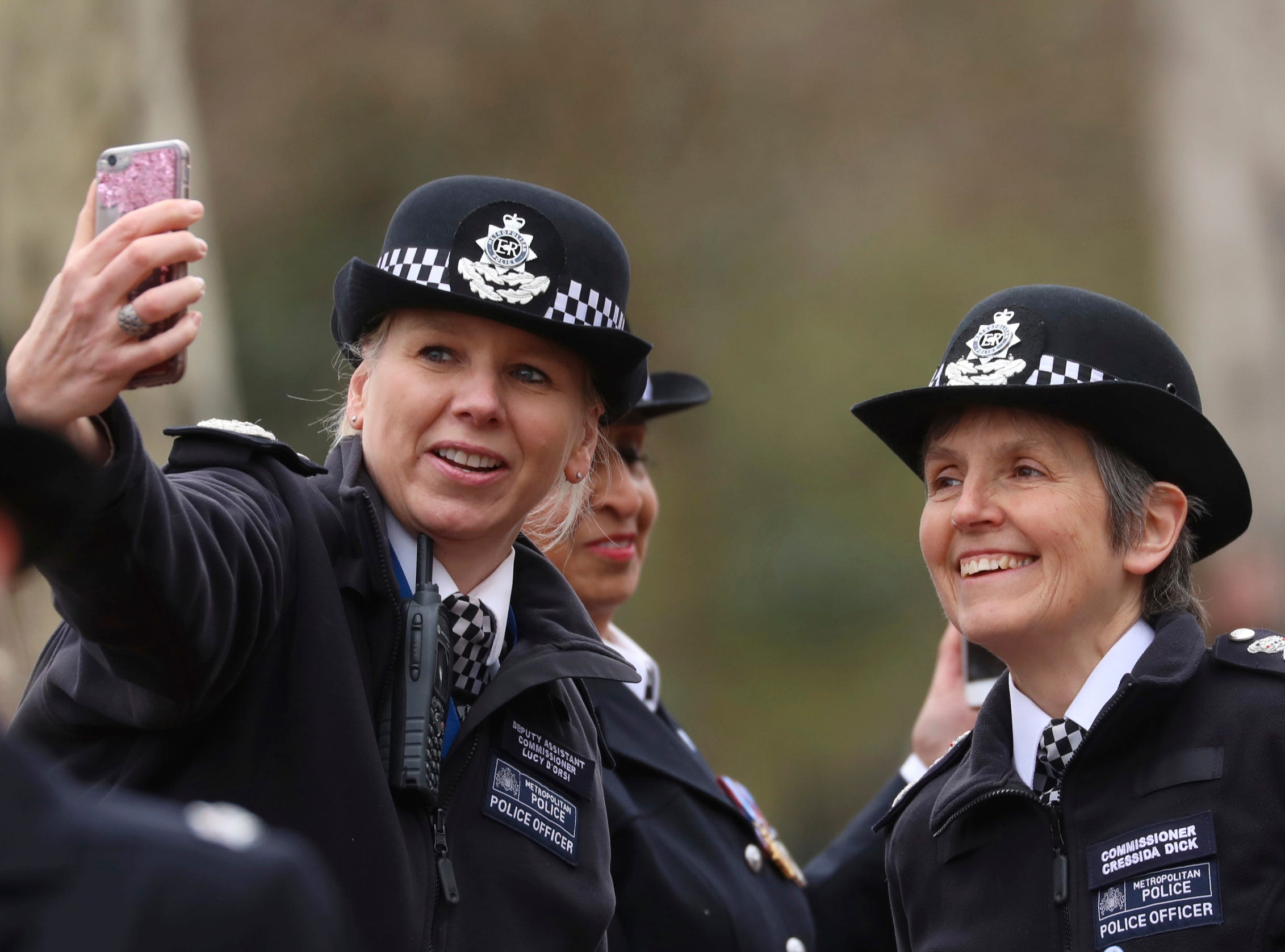 """A female police officer takes a selfie posing with Metropolitan Police Commissioner Cressida Dick, right, at the """"100 Years Strong Procession"""" in central London to mark International Women's Day, Friday March 8, 2019.  The procession supports IWD, and marks 100-years since women were allowed to join the the Metropolitan Police. (Isabel Infantes/PA via AP)"""