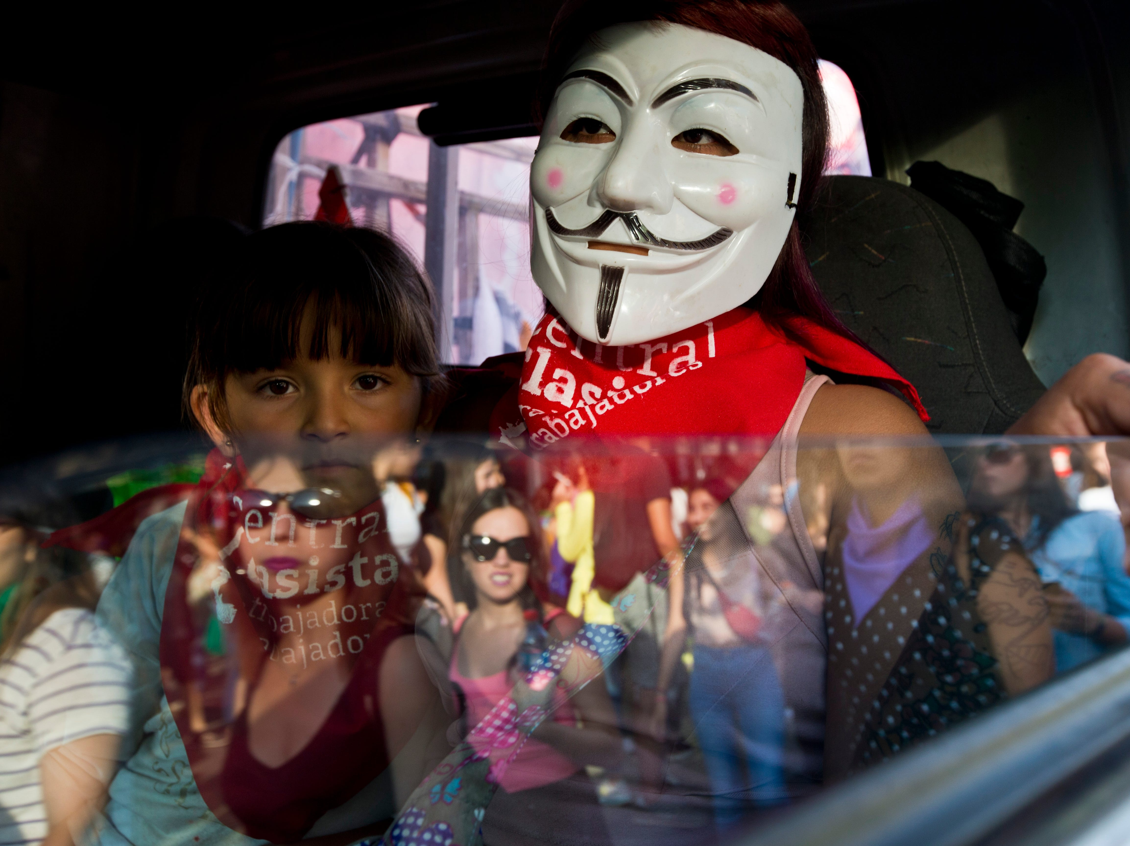 A woman wearing a mask and a girl ride inside a truck during a march marking International Women's Day in Santiago, Chile, Friday, March 8, 2019. The day has been sponsored by the United Nations since 1975 as millions of women around the world are demanding equality amid a persistent salary gap, violence and widespread inequality. (AP Photo/Esteban Felix)