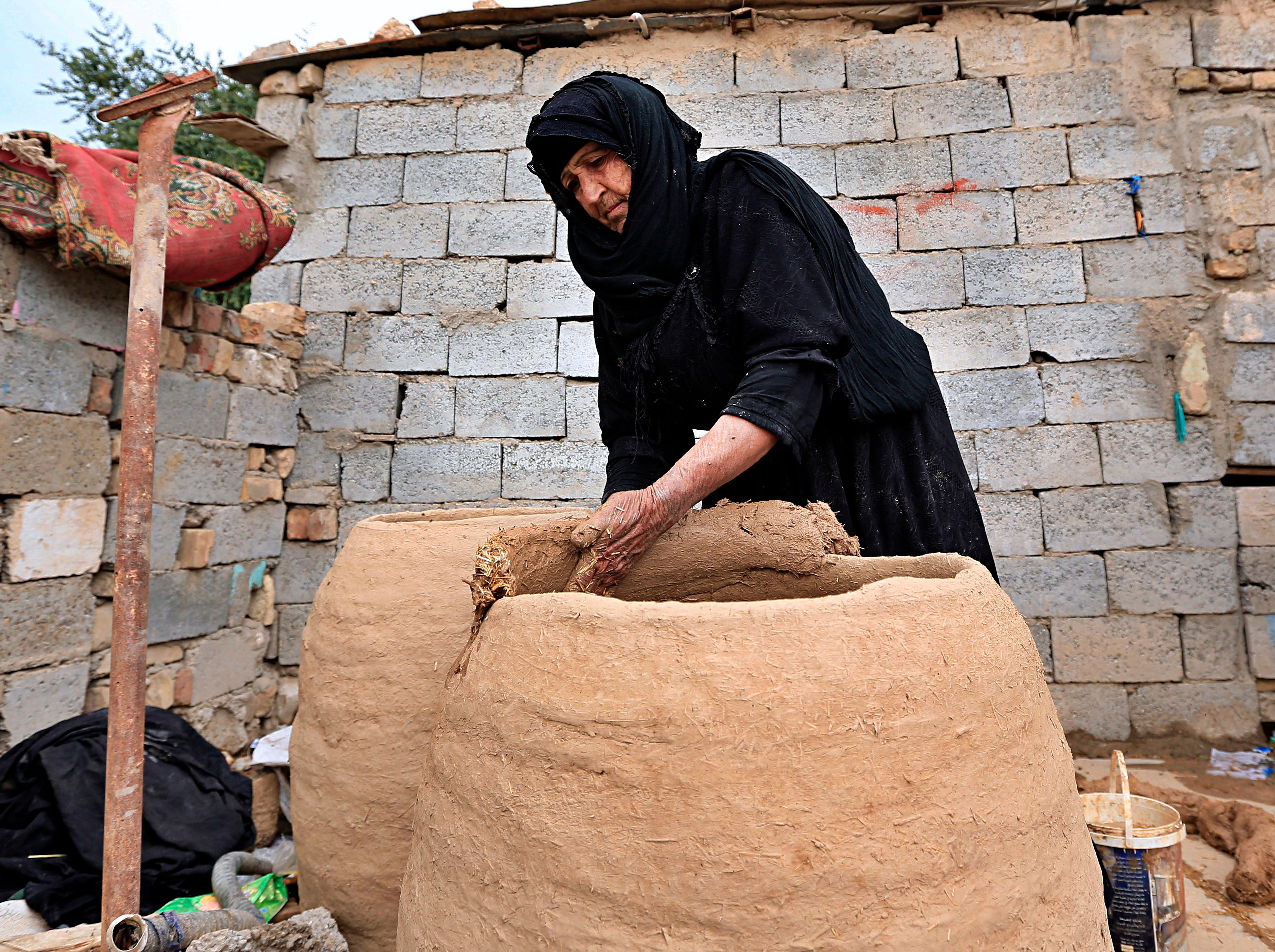 An Iraqi woman builds rough-hewn clay tureens used for cooking bread over a wood fire, at her home as the world celebrates International Women's Day in Baghdad, Iraq, Friday, March 8, 2019. (AP Photo/Hadi Mizban)
