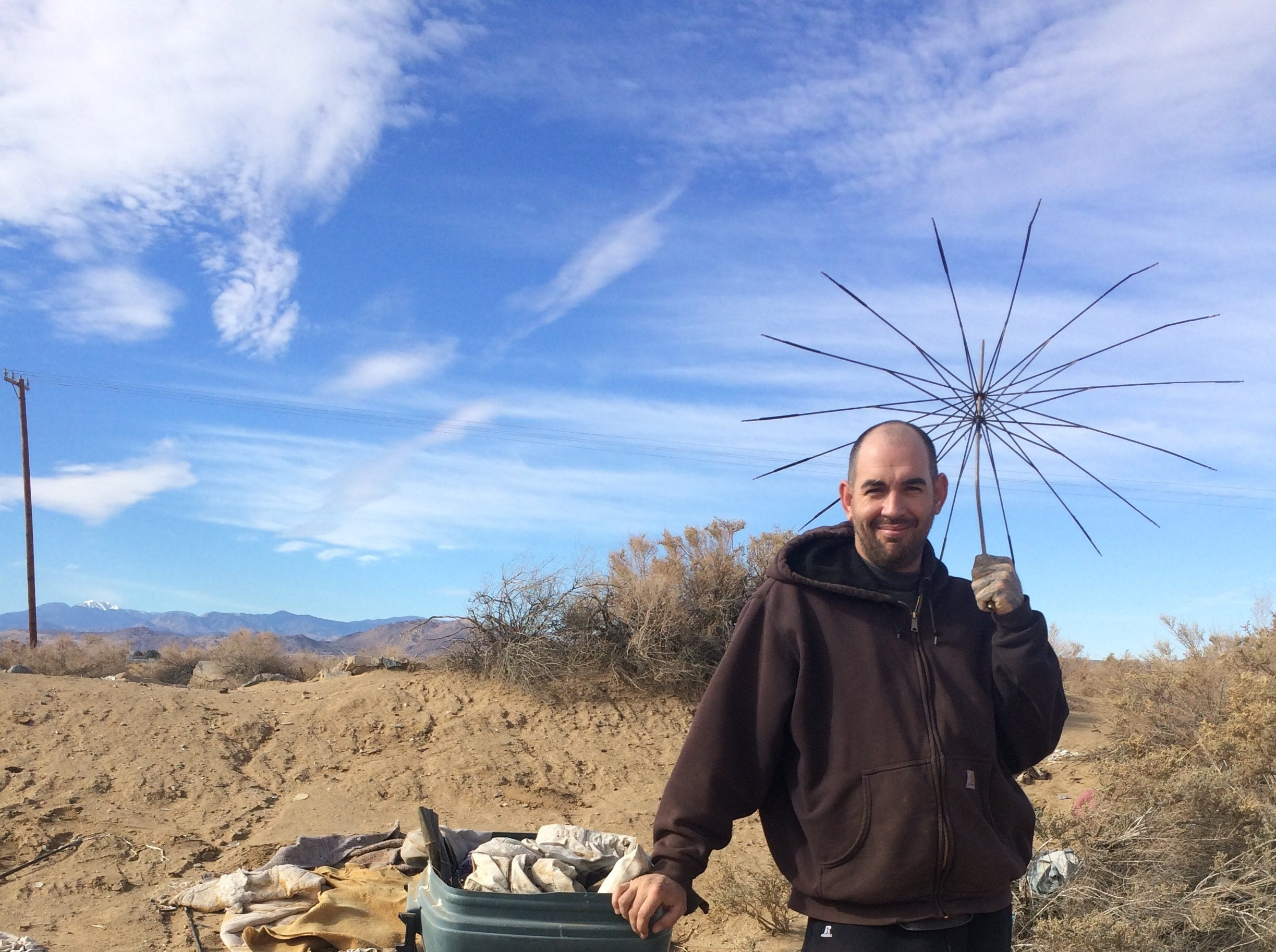 Colin Sauter, of Joshua Tree, poses with an umbrella he found while cleaning up trash in the open desert.