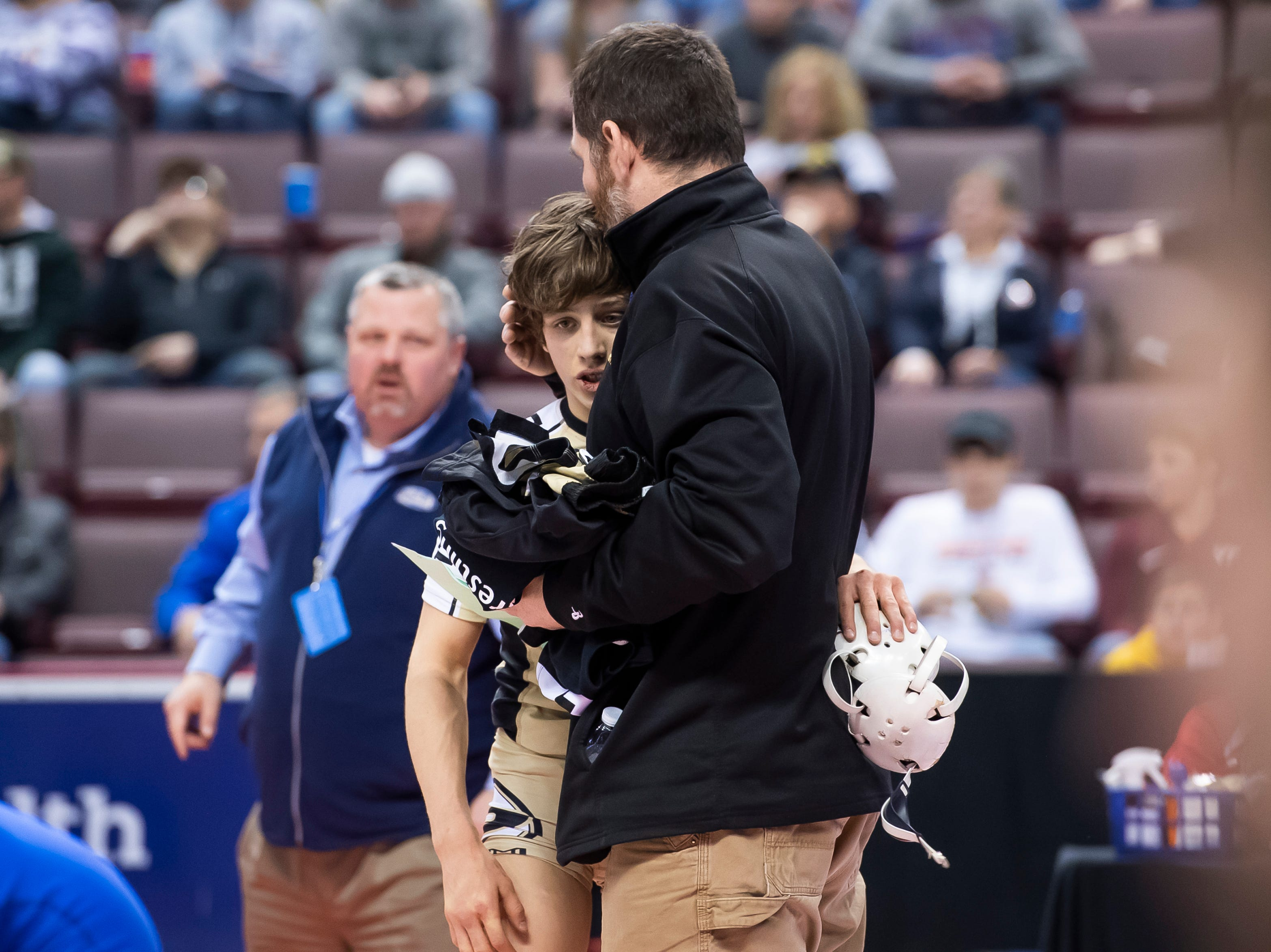 Biglerville's Levi Haines gets a hug from his dad and coach Ken Haines after defeating Chestnut Ridge's Kai Burkett during the 2A 106-pound semifinal bout at the Giant Center in Hershey Friday, March 8, 2019. Haines won by major decision 8-0.