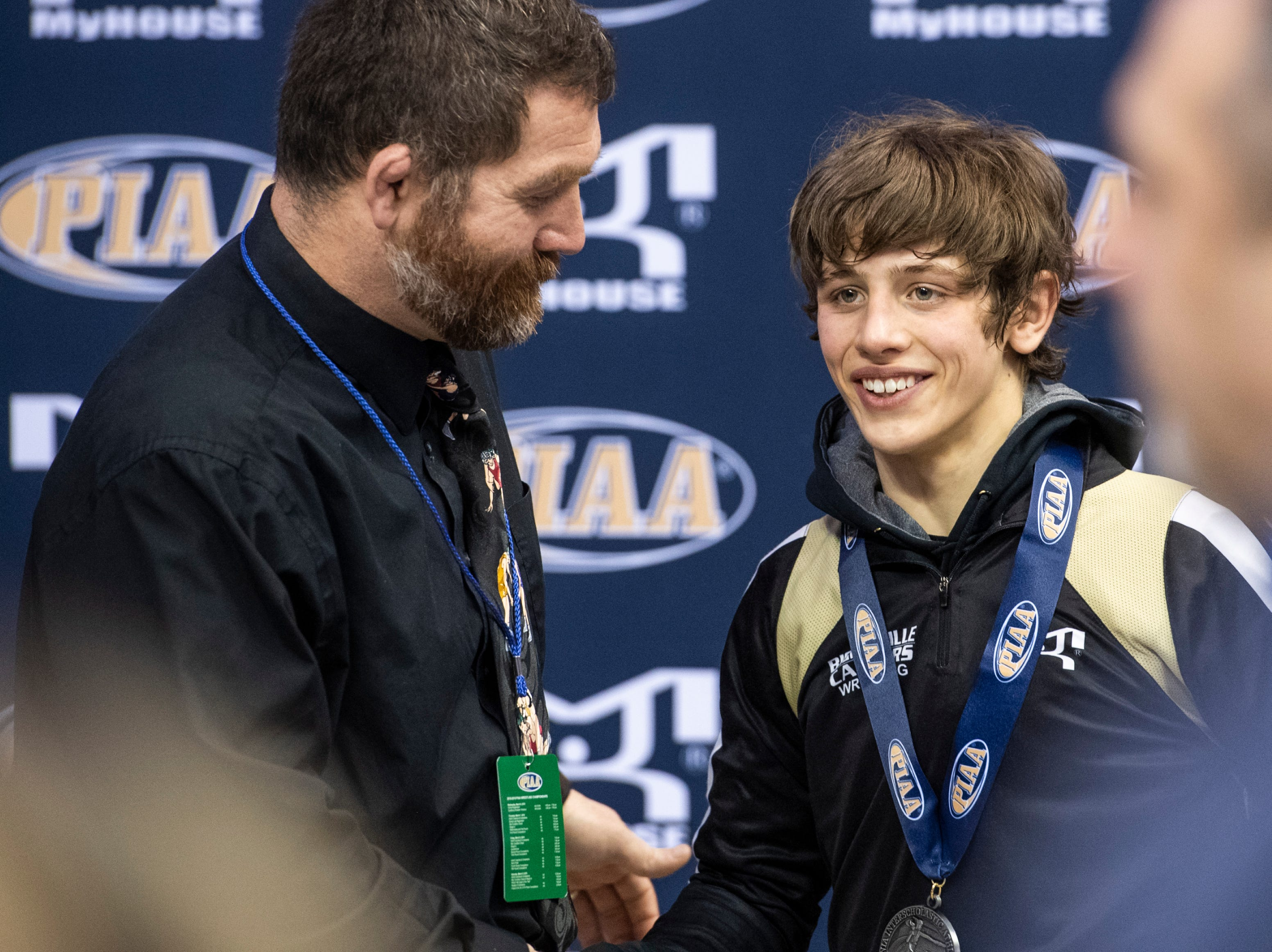 Biglerville's Levi Haines is awarded the silver medal by his dad and coach, Ken Haines, following the PIAA 2A 106-pound championship bout at the Giant Center in Hershey Saturday, March 9, 2019.