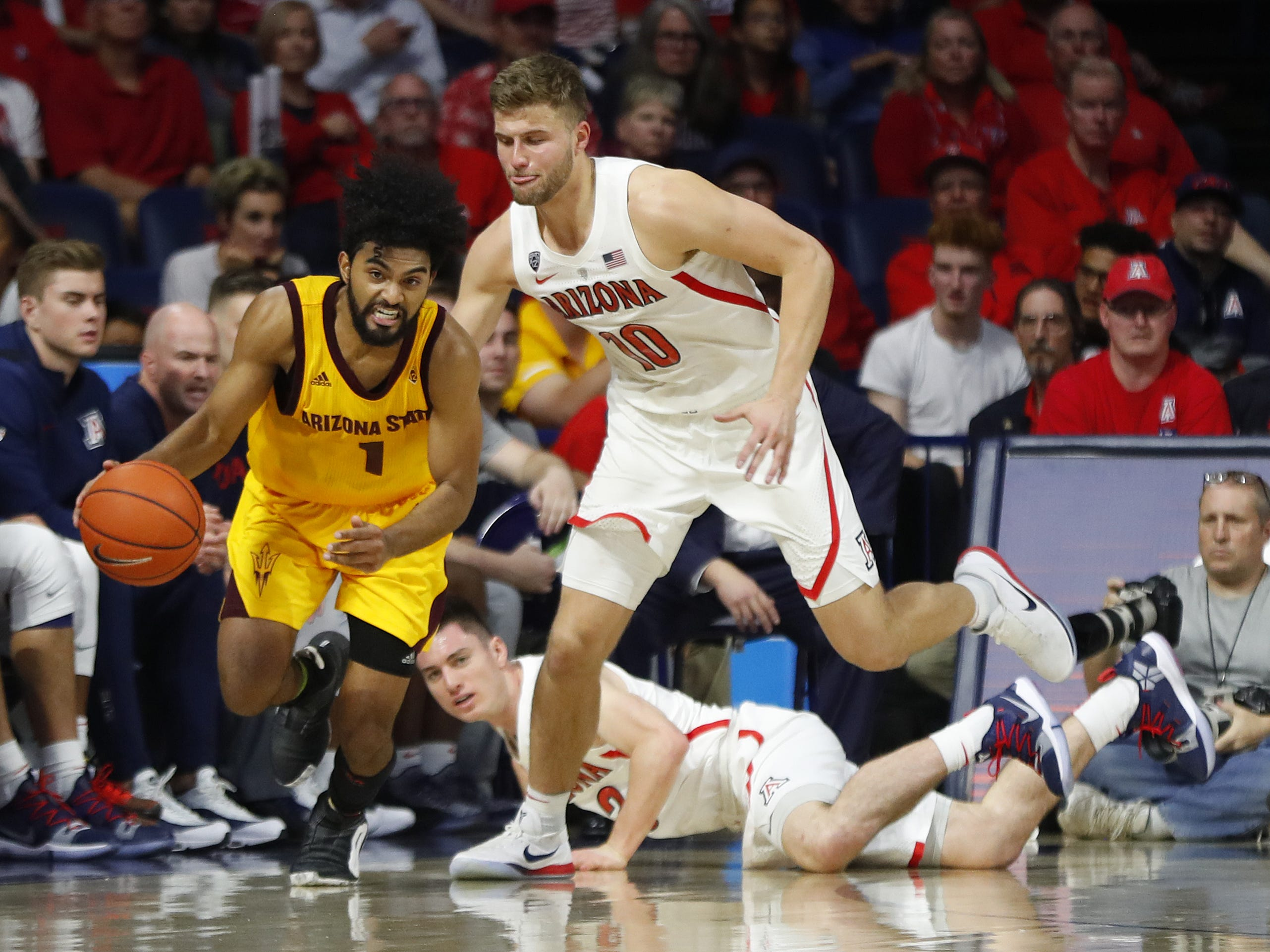ASU's Remy Martin (1) dribbles the ball up the court away from Arizona's Ryan Luther (10) during the second half at the McKale Memorial Center in Tucson, Ariz. on March 9, 2019.