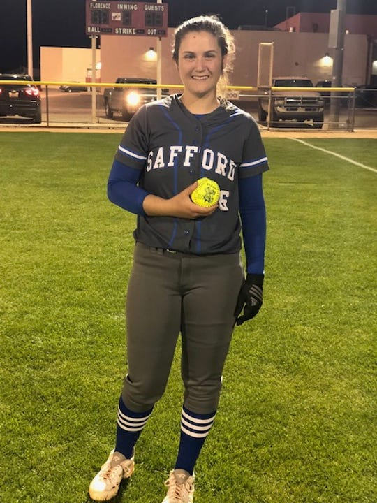 Safford senior Kristin Cocke holds the game ball after surpassing 1,000 strikeouts in her high school career.
