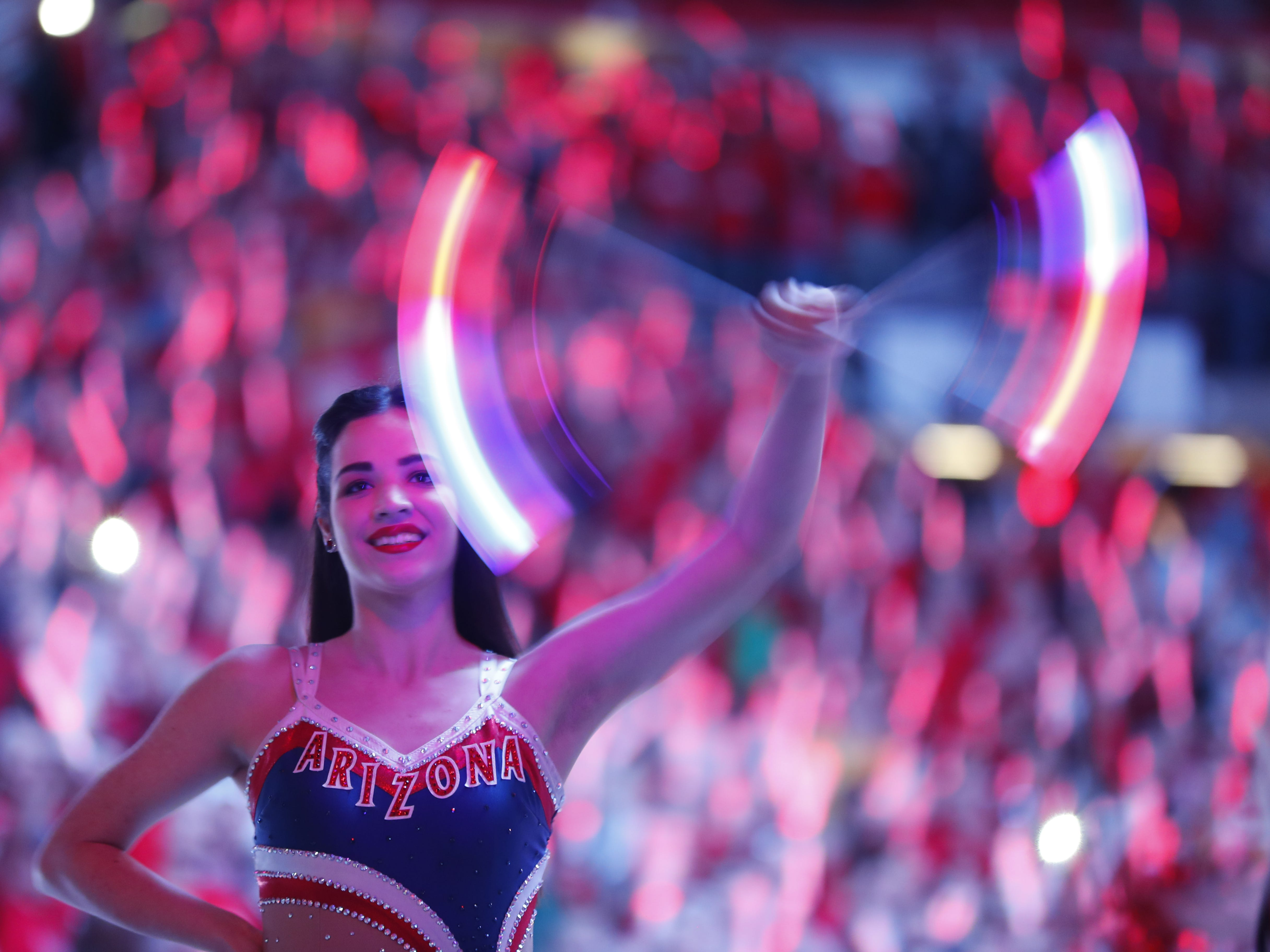 An Arizona cheerleader twirls her light up baton during the pregame at the McKale Memorial Center in Tucson, Ariz. on March 9, 2019.