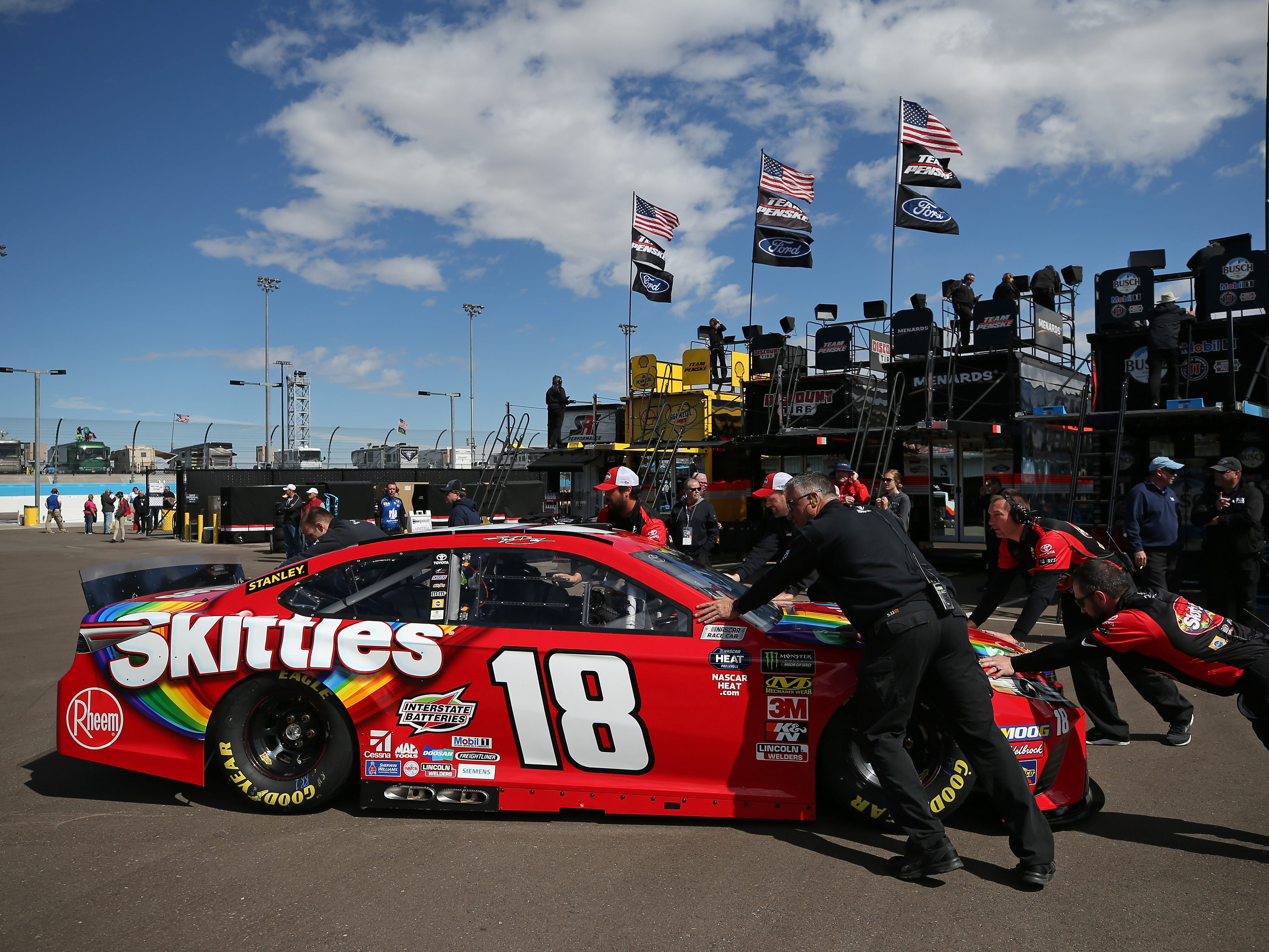 AVONDALE, AZ - MARCH 08:  Kyle Busch, driver of the #18 Skittles Toyota, has his car pushed throught the garage during practice for the Monster Energy NASCAR Cup Series TicketGuardian 500 at ISM Raceway on March 8, 2019 in Avondale, Arizona.