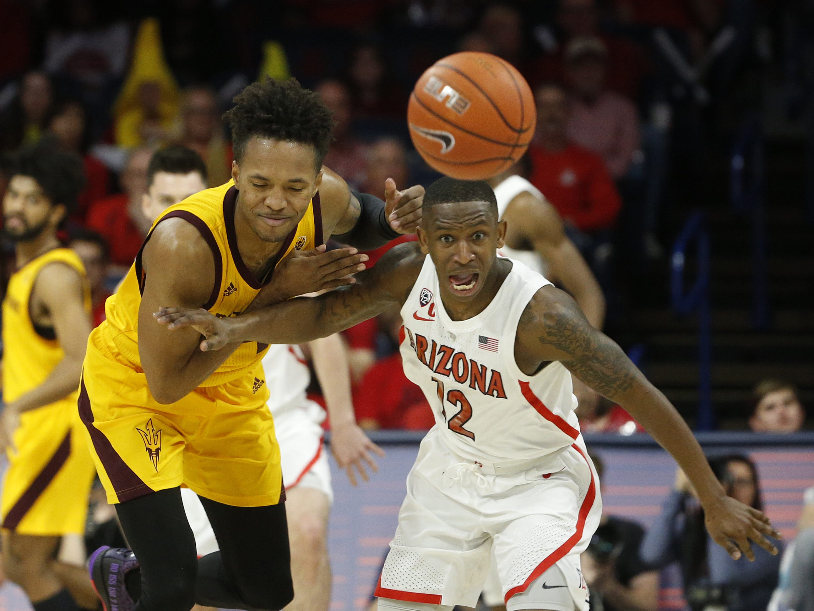 Arizona's Justin Coleman (12) steals the ball from ASU's Kamani Lawrence (14) during the first half at the McKale Memorial Center in Tucson, Ariz. on March 9, 2019.