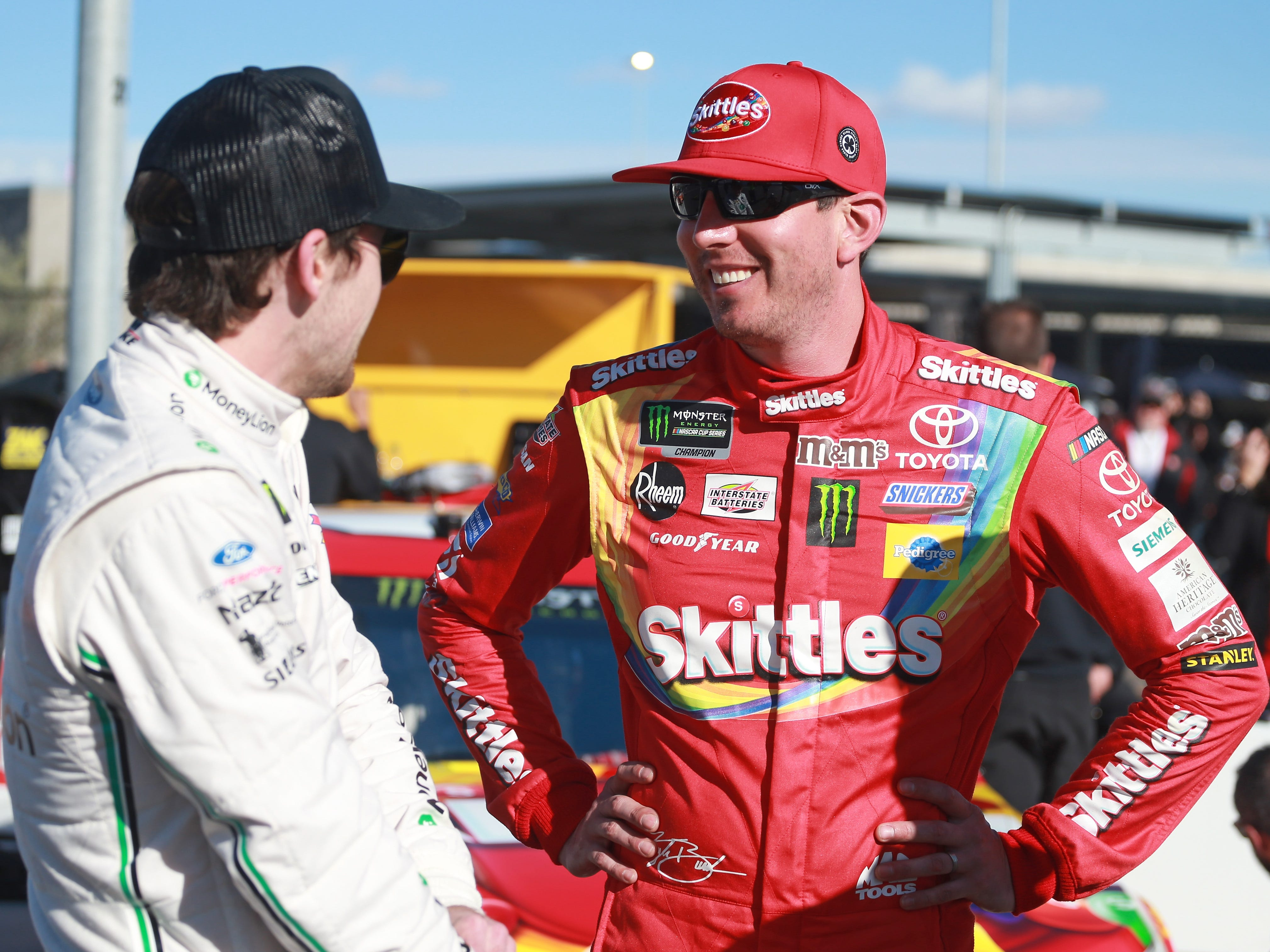 AVONDALE, AZ - MARCH 08:  Kyle Busch, driver of the #18 Skittles Toyota, talks with Ryan Blaney, driver of the #12 MoneyLion Ford, during qualifying for the Monster Energy NASCAR Cup Series TicketGuardian 500 at ISM Raceway on March 8, 2019 in Avondale, Arizona.