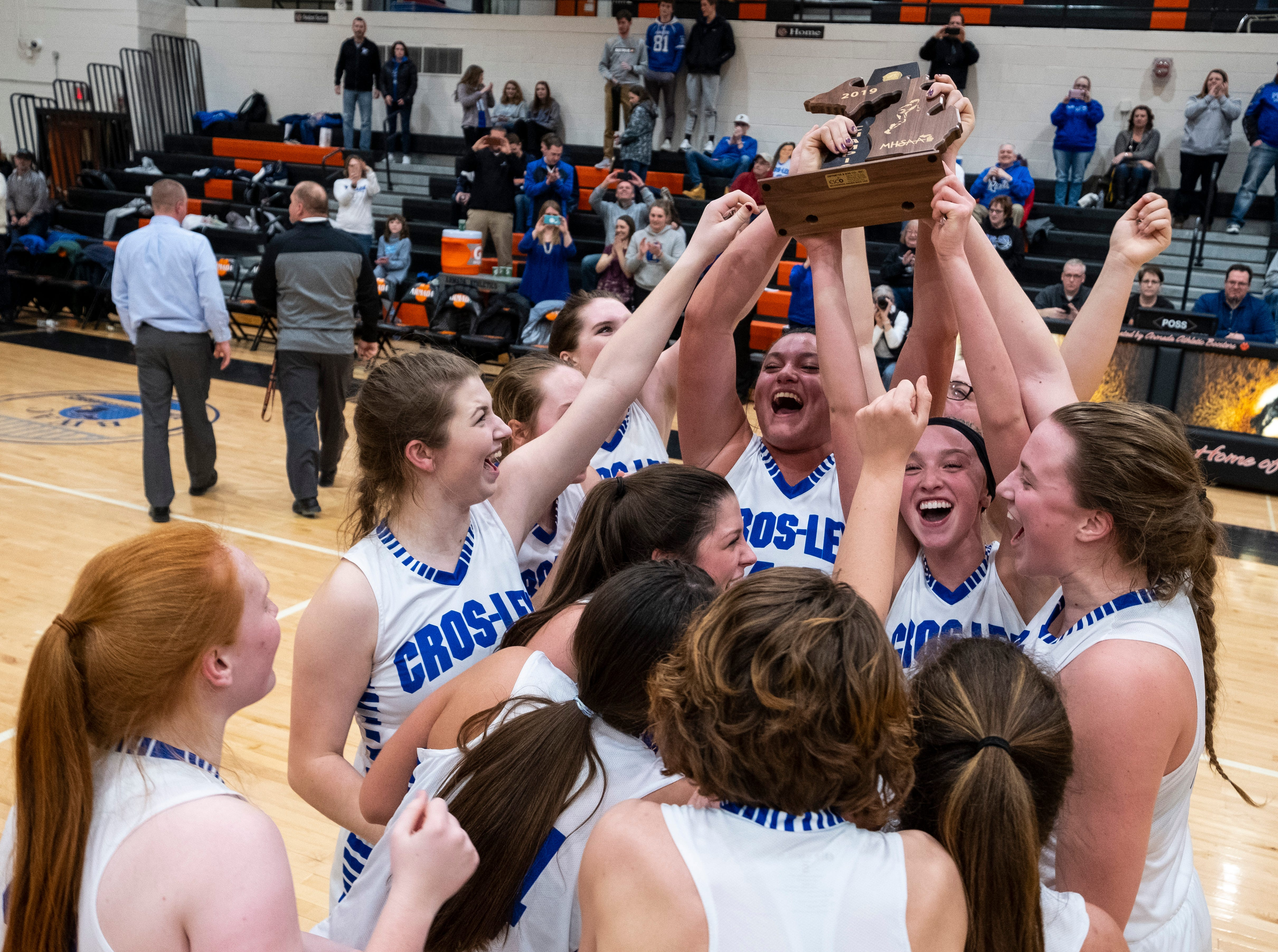 The Croswell-Lexington High School girls basketball team celebrate their victory over Marysville High School in the MHSAA Division 2 girls basketball district finals Friday, March 8, 2019 at Armada High School.