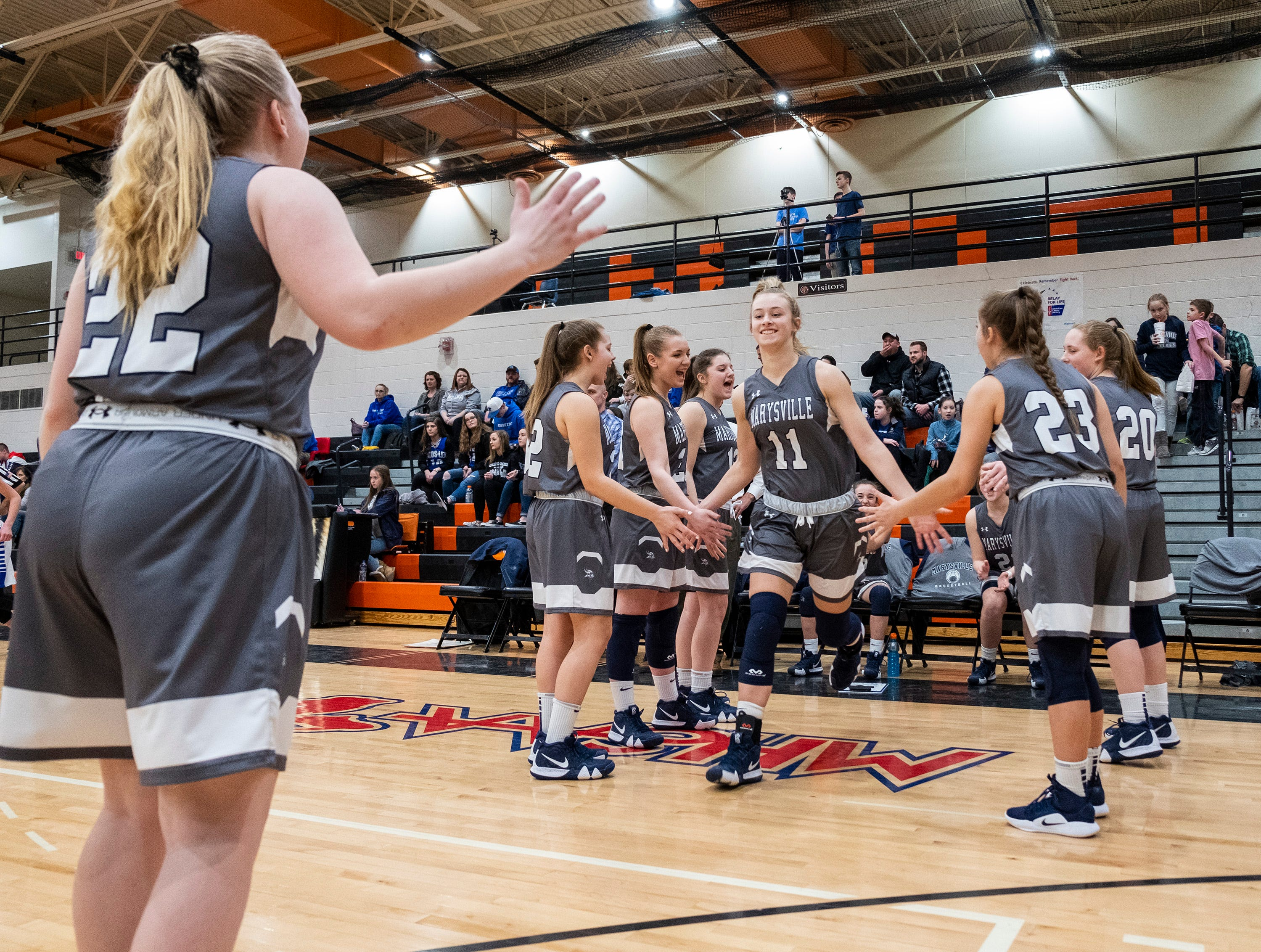 Marysville's Gabby Fogarty (11) high-fives her teammates as she takes the court before the MHSAA Girls Basketball Division 2 district finals against Croswell-Lexington High School Friday, March 8, 2019 at Armada High School.