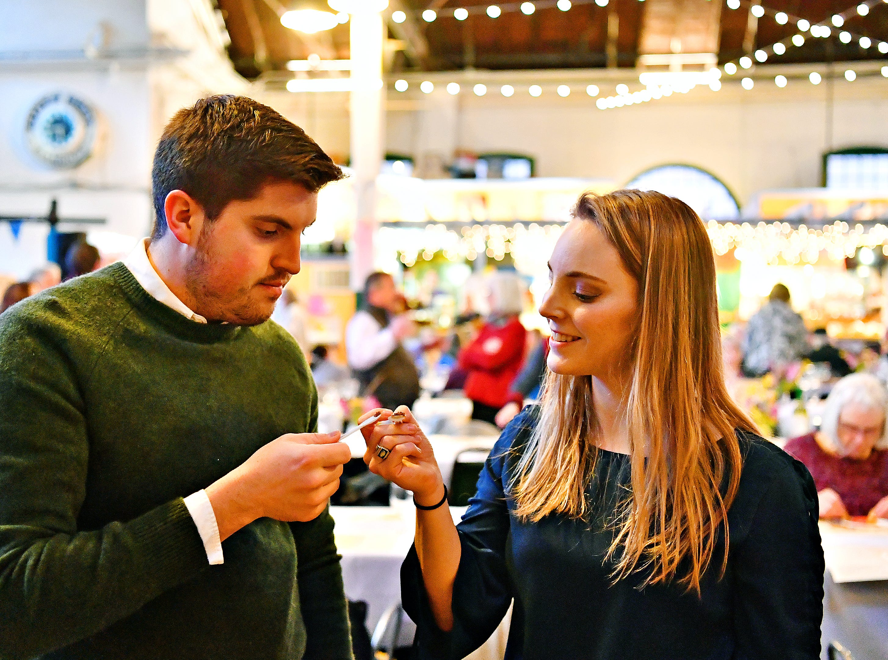 "Doug Hammond, left, and Katie Hammond, both of York City, ""toast"" with their tiny spoons while tasting honey during the York County Beekeepers' Association Centennial Banquet at Central Market in York City, Friday, March 8, 2019. The Hammonds, invited to the banquet by friends, plan to begin their beekeeping journey within the next couple of months. Dawn J. Sagert photo"
