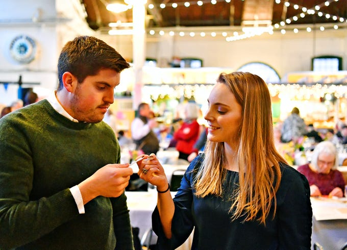 """Doug Hammond, left, and Katie Hammond, both of York City, """"toast"""" with their tiny spoons while tasting honey during the York County Beekeepers' Association Centennial Banquet at Central Market in York City, Friday, March 8, 2019. The Hammonds, invited to the banquet by friends, plan to begin their beekeeping journey within the next couple of months. Dawn J. Sagert photo"""