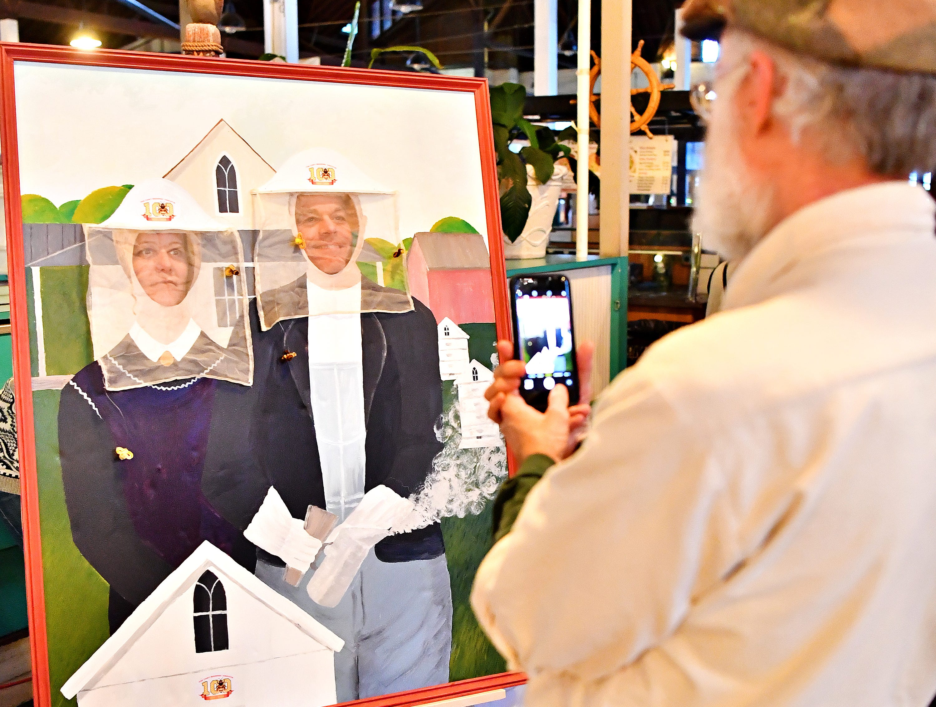 From right, York County artist Robert Ought, right, of Hellam Township, takes a photo of Matt and Christine Rhoads, of Lancaster City, during the York County Beekeepers' Association Centennial Banquet at Central Market in York City, Friday, March 8, 2019. Dawn J. Sagert photo